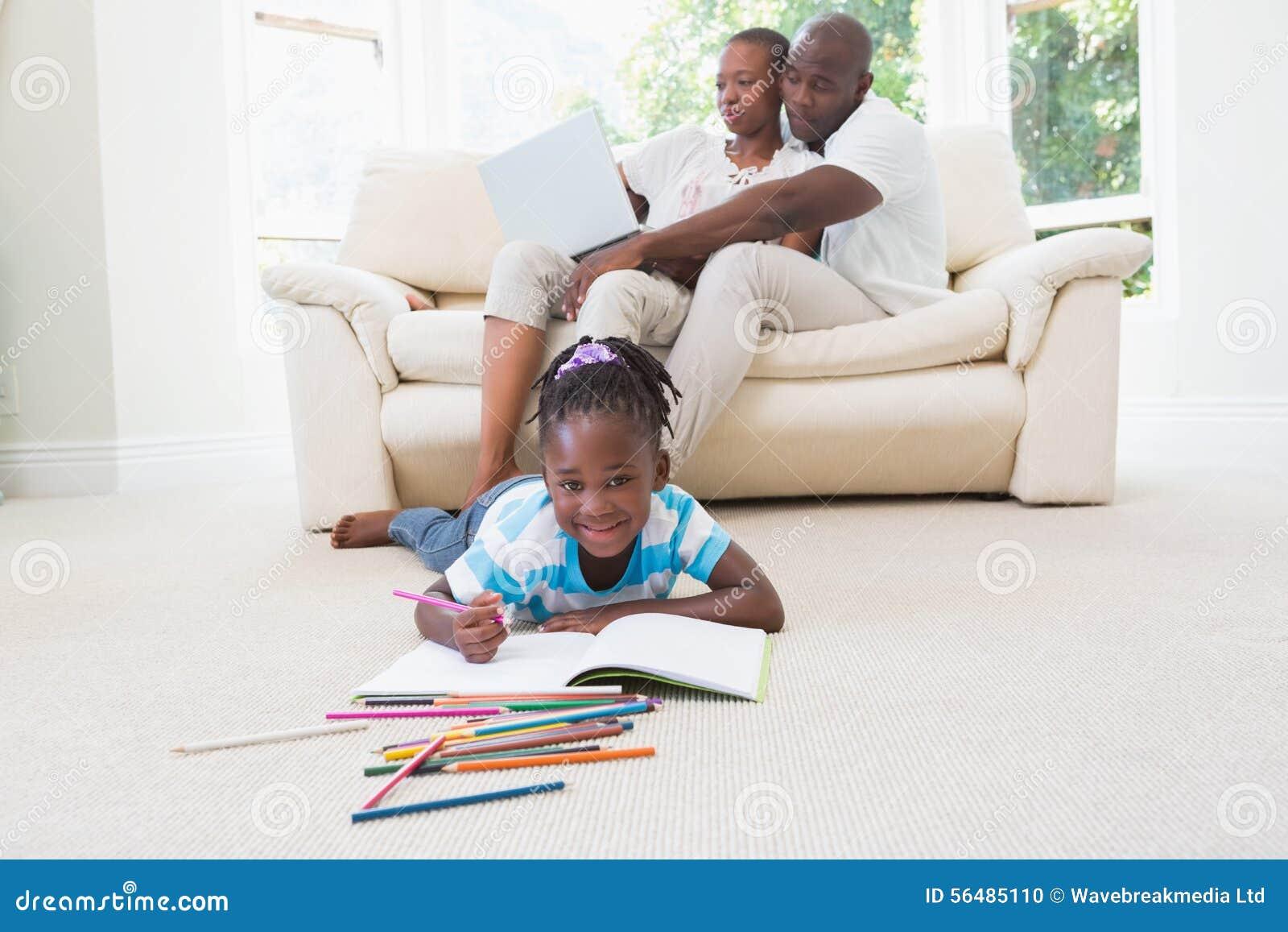 Jolis couples utilisant l ordinateur portable sur le divan et leur dessin de fille