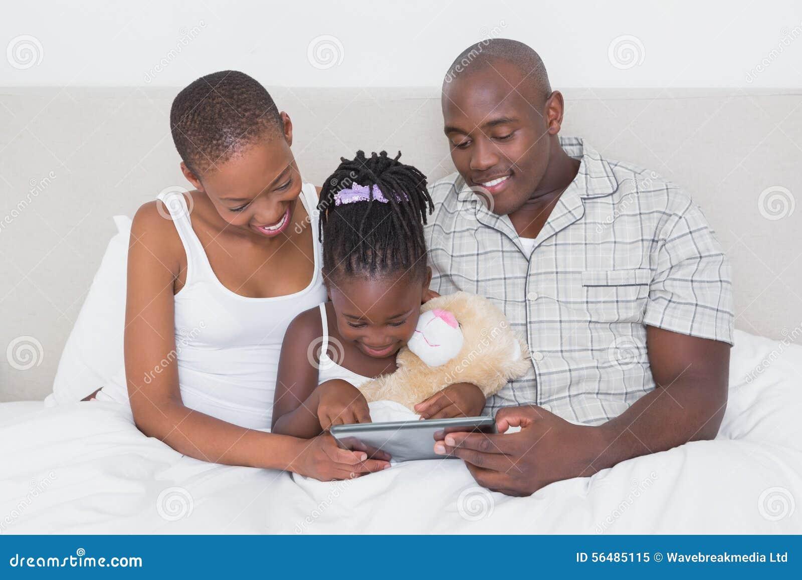 Jolis couples utilisant le comprimé avec leur fille dans le lit