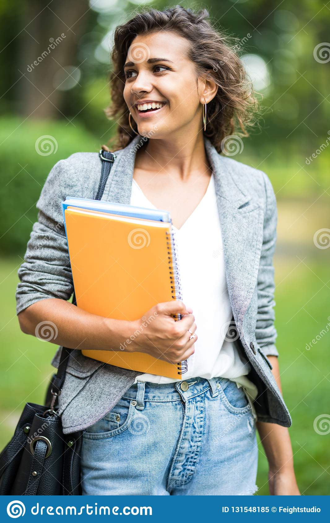 Jolly carefree girl embracing books in park while coming home after classes in university. Cheerful attractive young woman looking