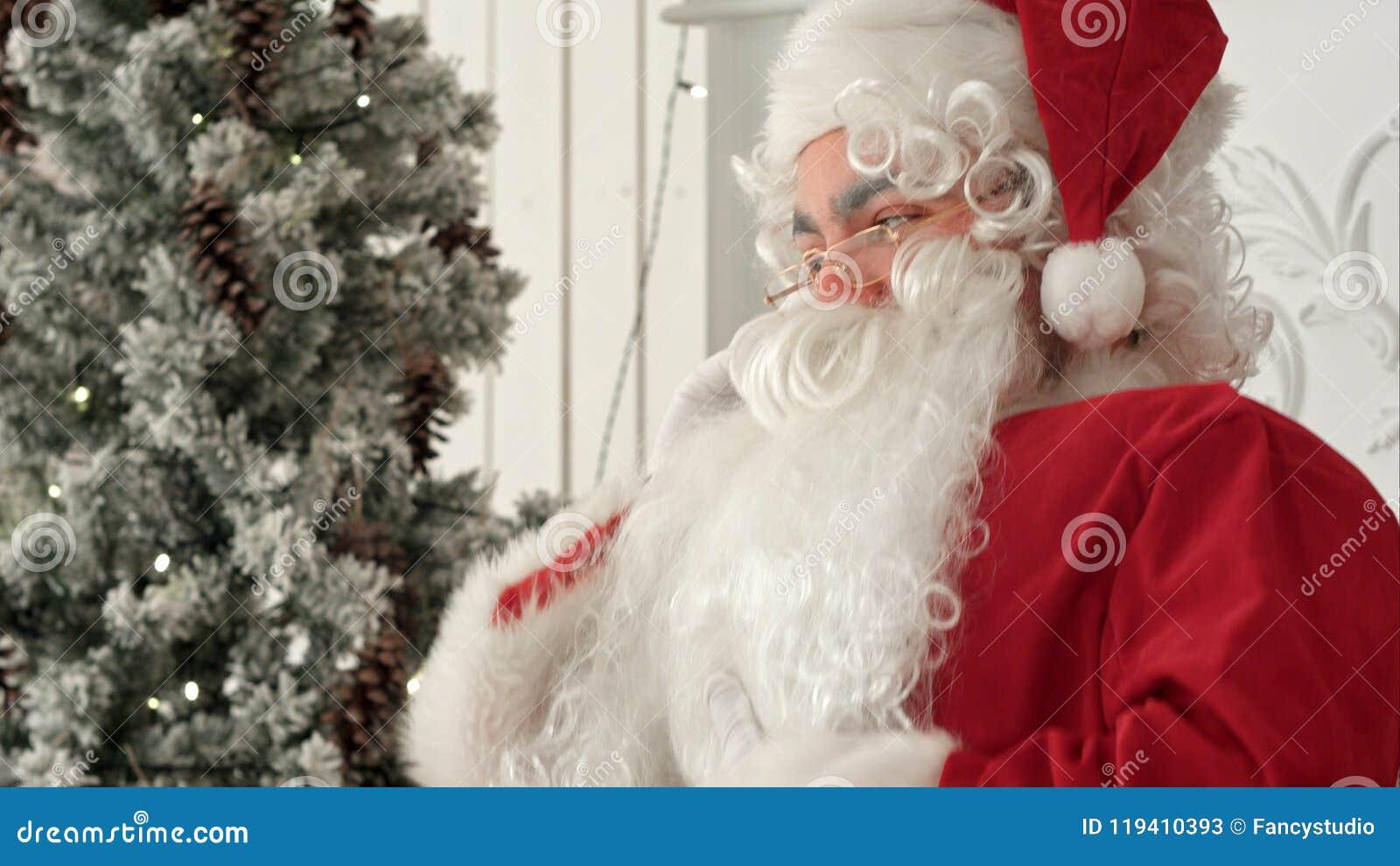Jolly Santa Claus sammanträde vid julgranen och samtal på telefonen