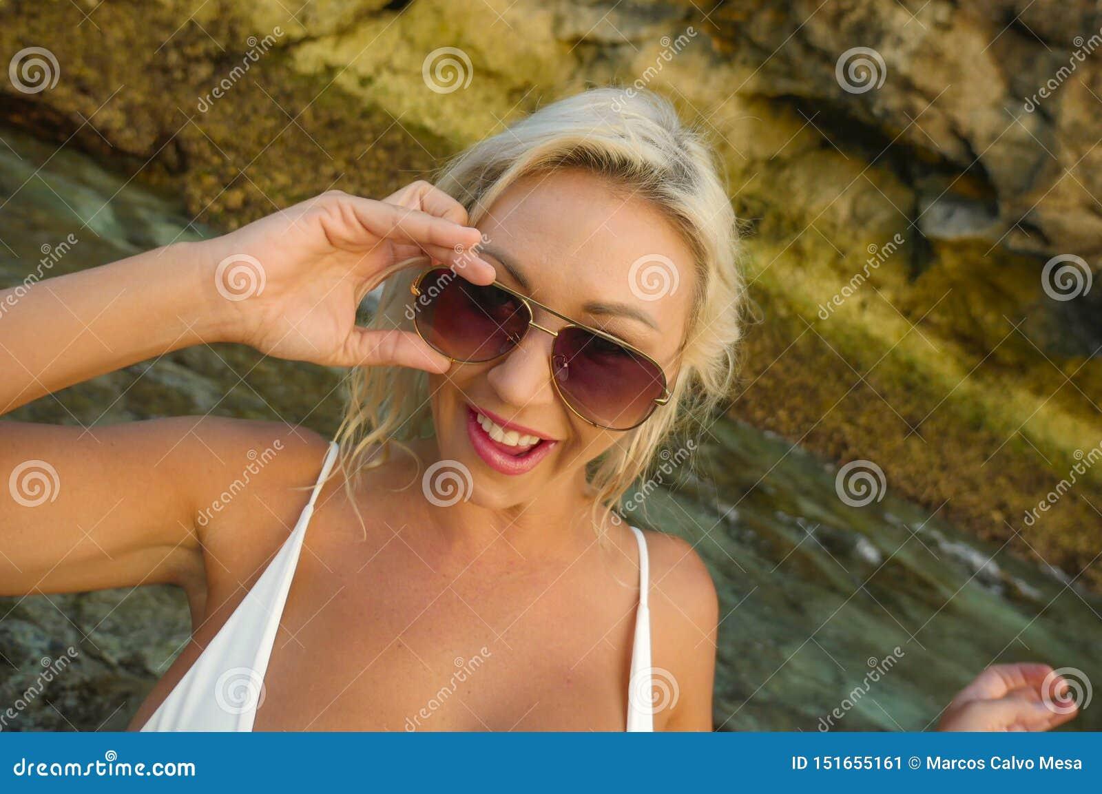 Jong aantrekkelijk gelukkig en vrolijk blond meisje die in bikini het speelse holdingszonnebril stellen glimlachen onbezorgd bij