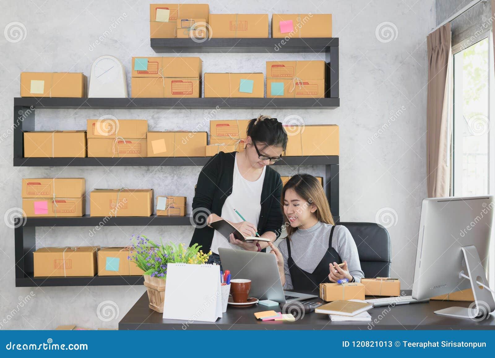 Jong Aziatisch ondernemerspartners of het bedrijfseigenaarswerk thuis bureau die klanten` s orde samen controleren