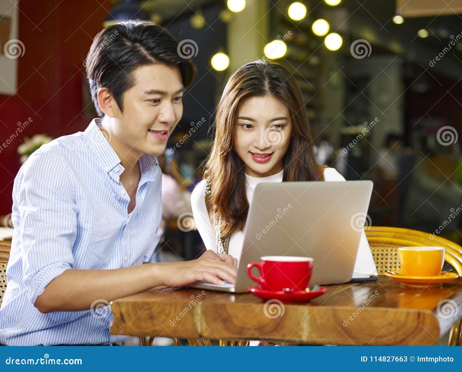 Jong Aziatisch paar die laptop in koffiewinkel met behulp van