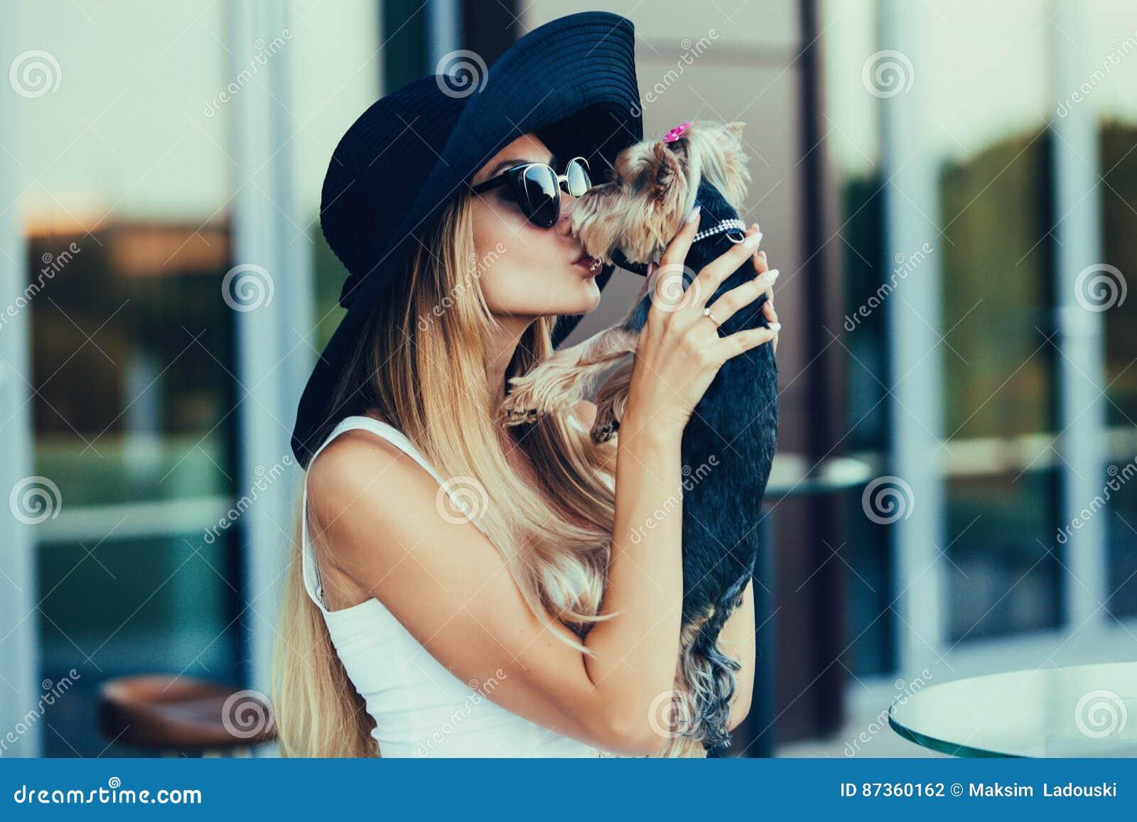 Jong blond meisje die kleine hond kussen