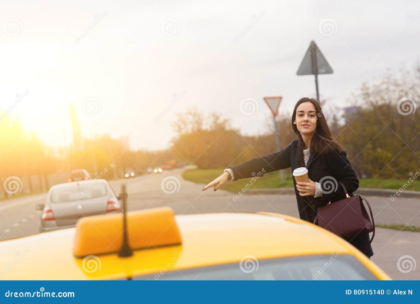 Jong brunette met de zak die van Bourgondië gele taxi stoping