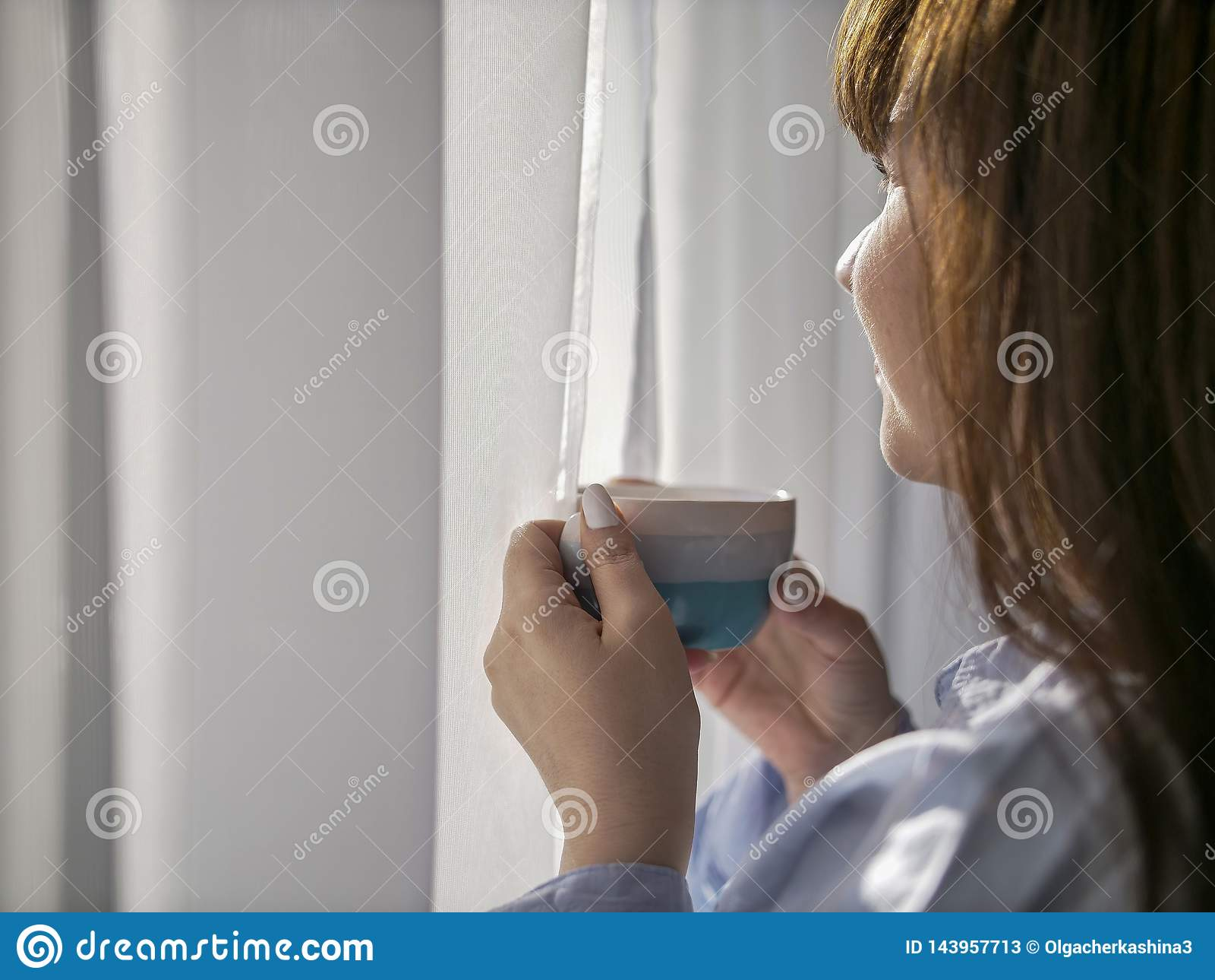 Jong brunette met een kop van koffie door het venster, close-up