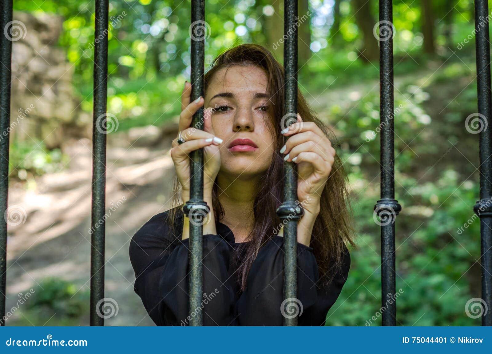 Jong charmant meisje de tiener met lange haarzitting achter de tralies in gevangenisgevangene in - Tiener meisje foto ...