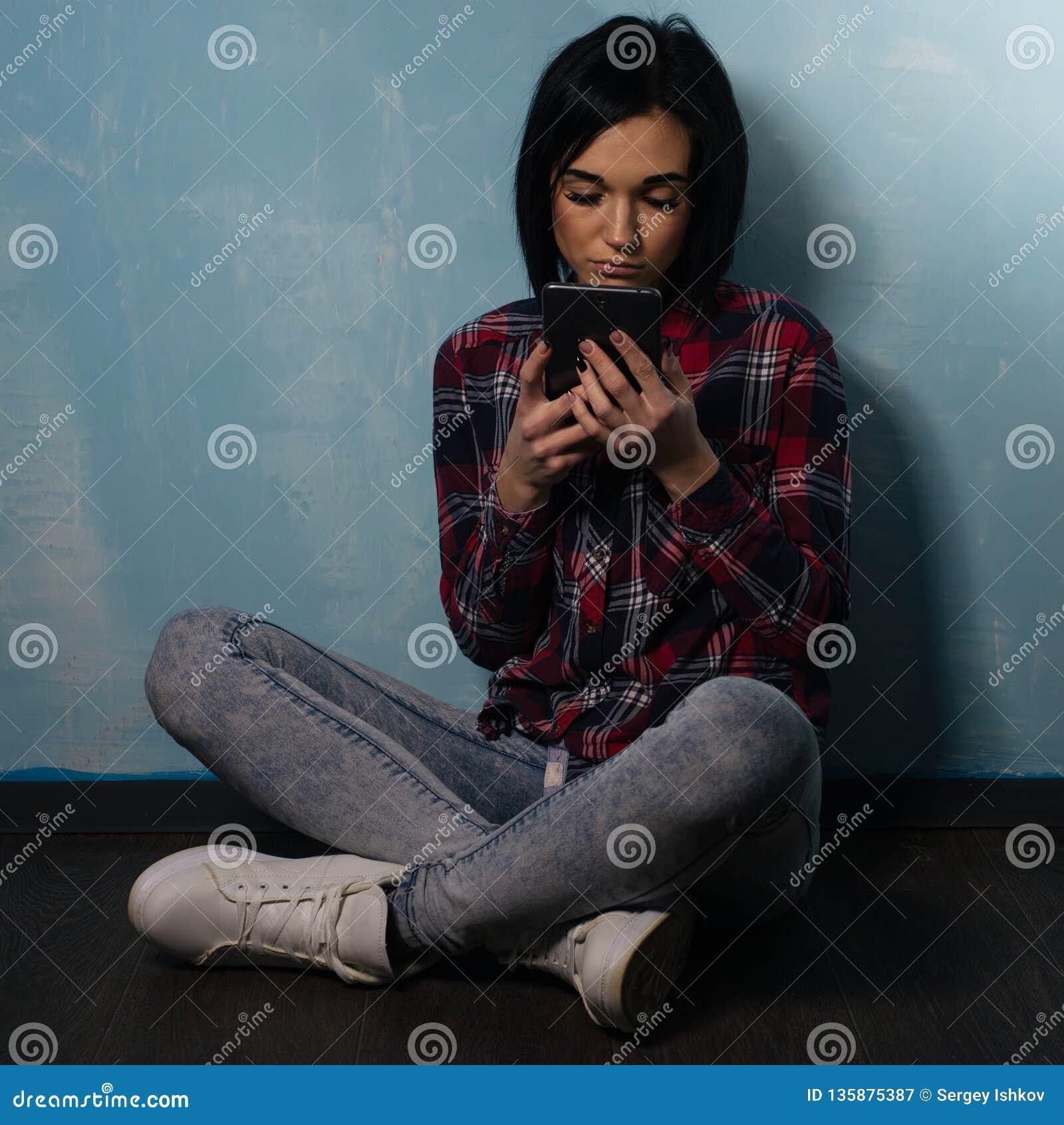 Jong droevig meisje die aan afhankelijkheid van sociale netwerken lijden die op de vloer met een smartphone zitten