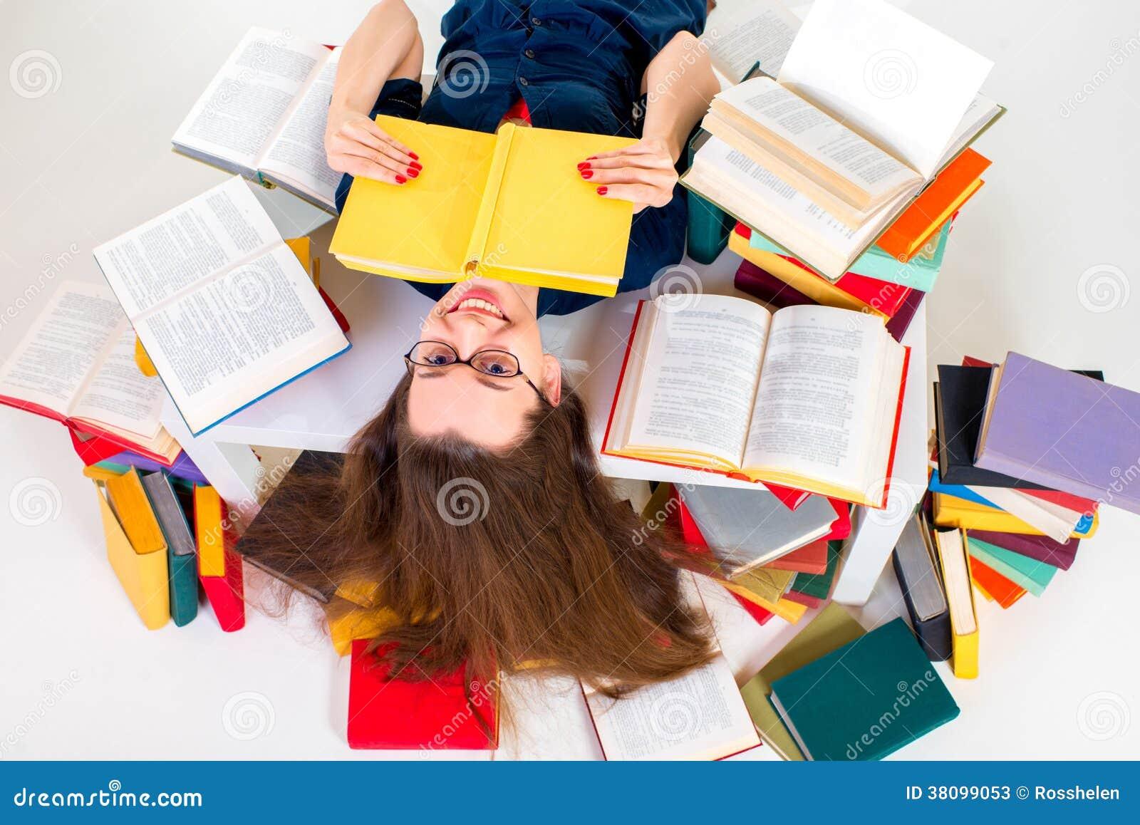 Jong en slim meisje die die met boek liggen door kleurrijk boek wordt omringd