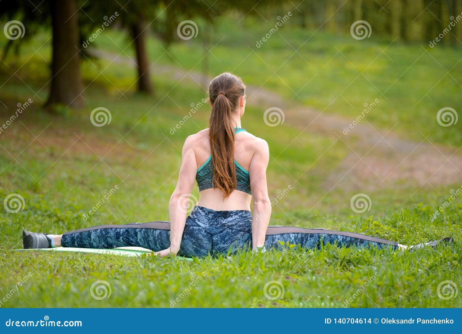 Jong flexibel meisje, die op de uitgerekte streng zitten, alvorens op te leiden