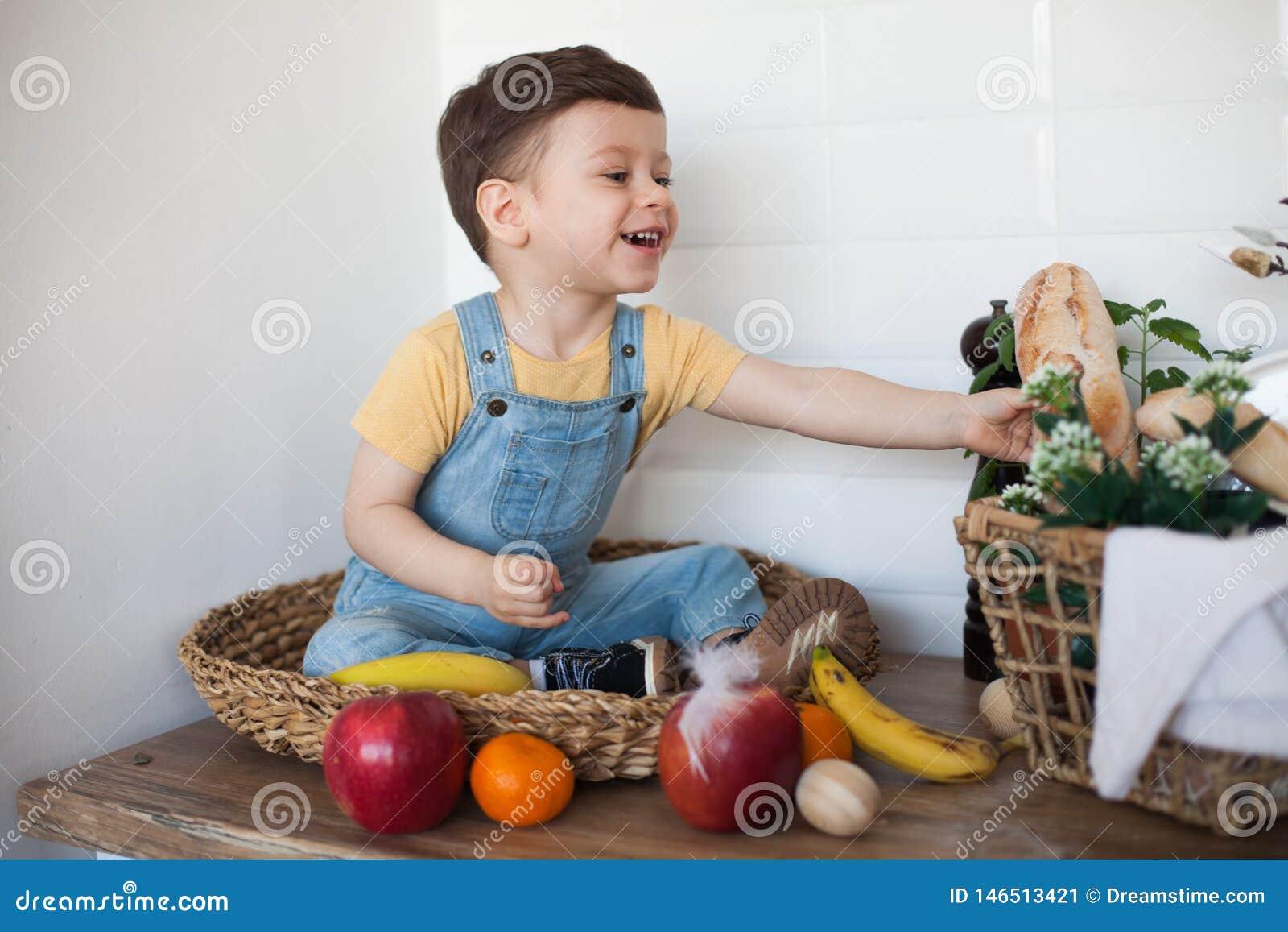 Jong geitje die een lijsthoogtepunt van natuurvoeding hebben Vrolijke peuter die gezonde salade en vruchten eten Baby die tussen