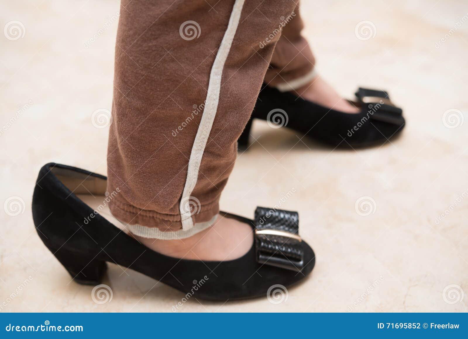 Jong geitje die mums in schoenen voor fu dragen