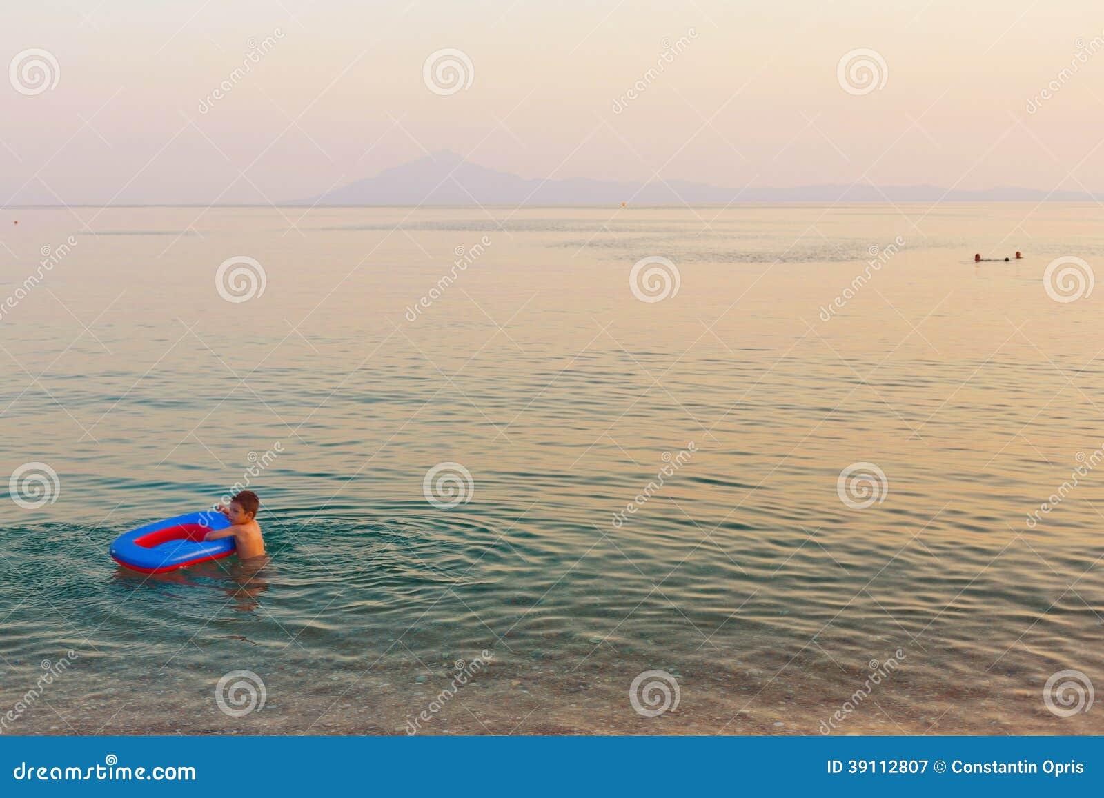 Jong geitje het spelen met opblaasbare boot