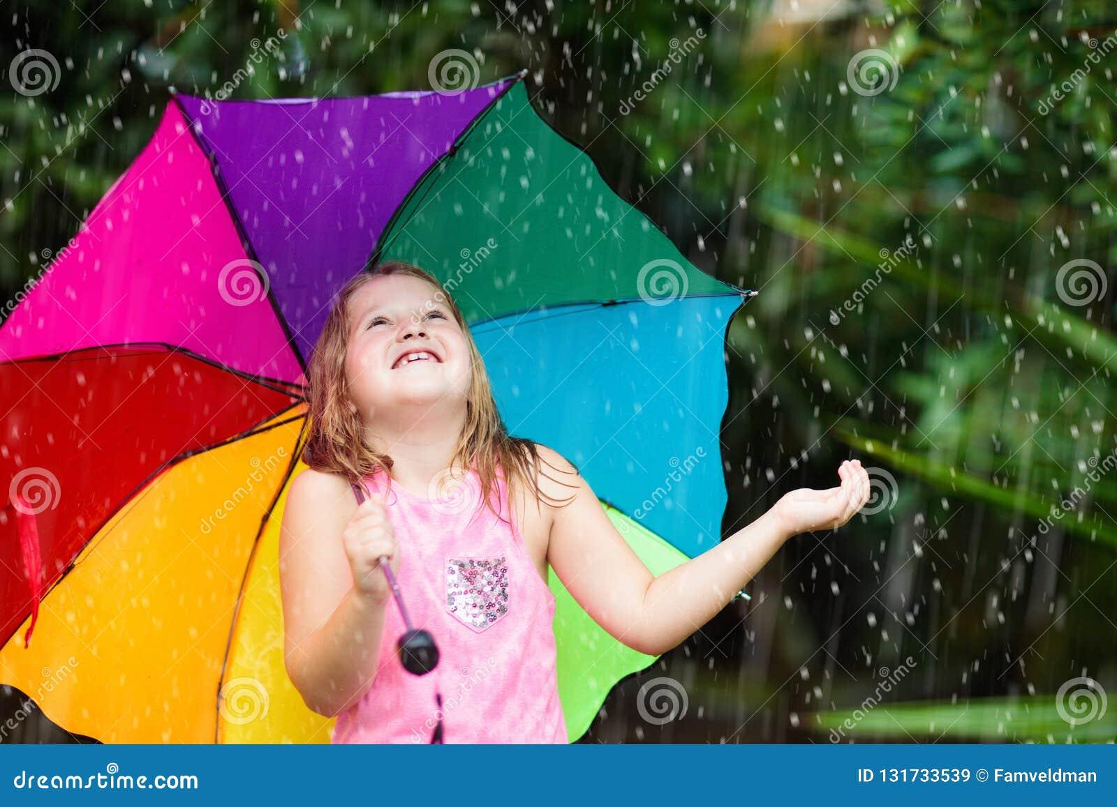 Jong geitje het spelen uit in de regen Kinderen met paraplu en regenlaarzenspel in openlucht in zware regen
