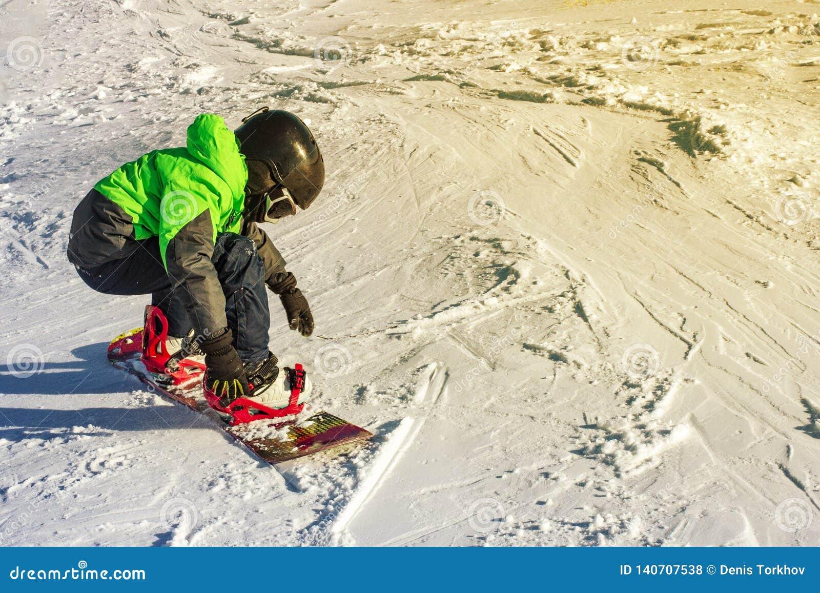 Jong geitje op snowboard in de aard van de de winterzonsondergang De sportfoto met geeft ruimte uit