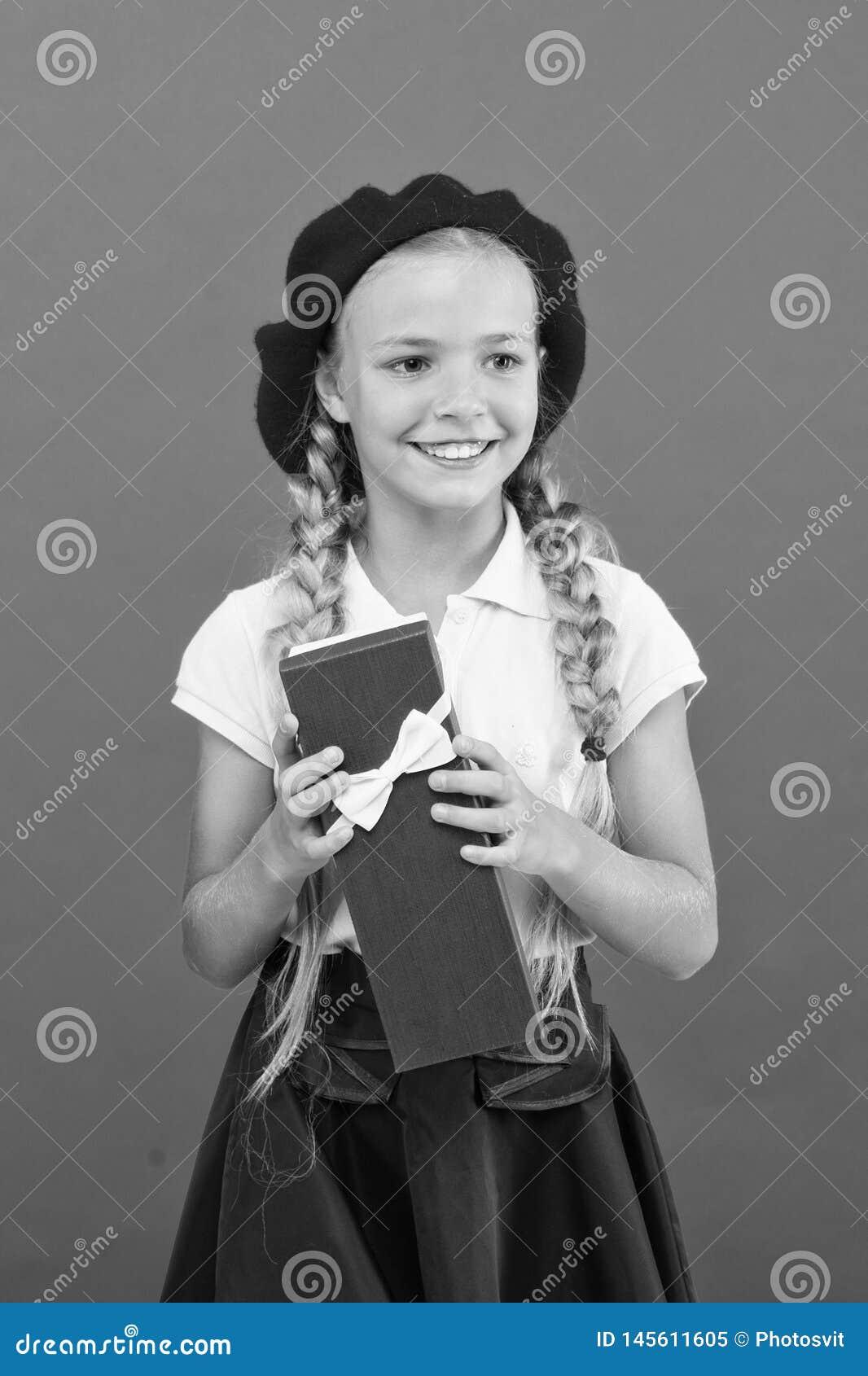 Jong geitjemeisje in eenvormige school en de giftdoos van de baretgreep Kind over het uitpakken van gift wordt opgewekt die Klein