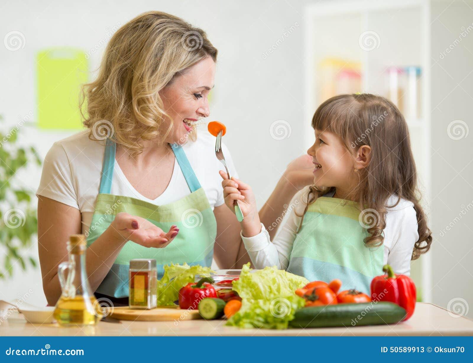 Jong geitjemeisje en moeder die gezonde voedselgroenten eten