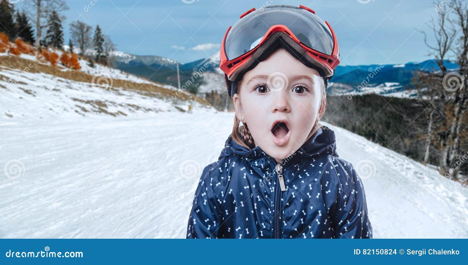Jong geitjemeisje in skitoestel op de winterachtergrond