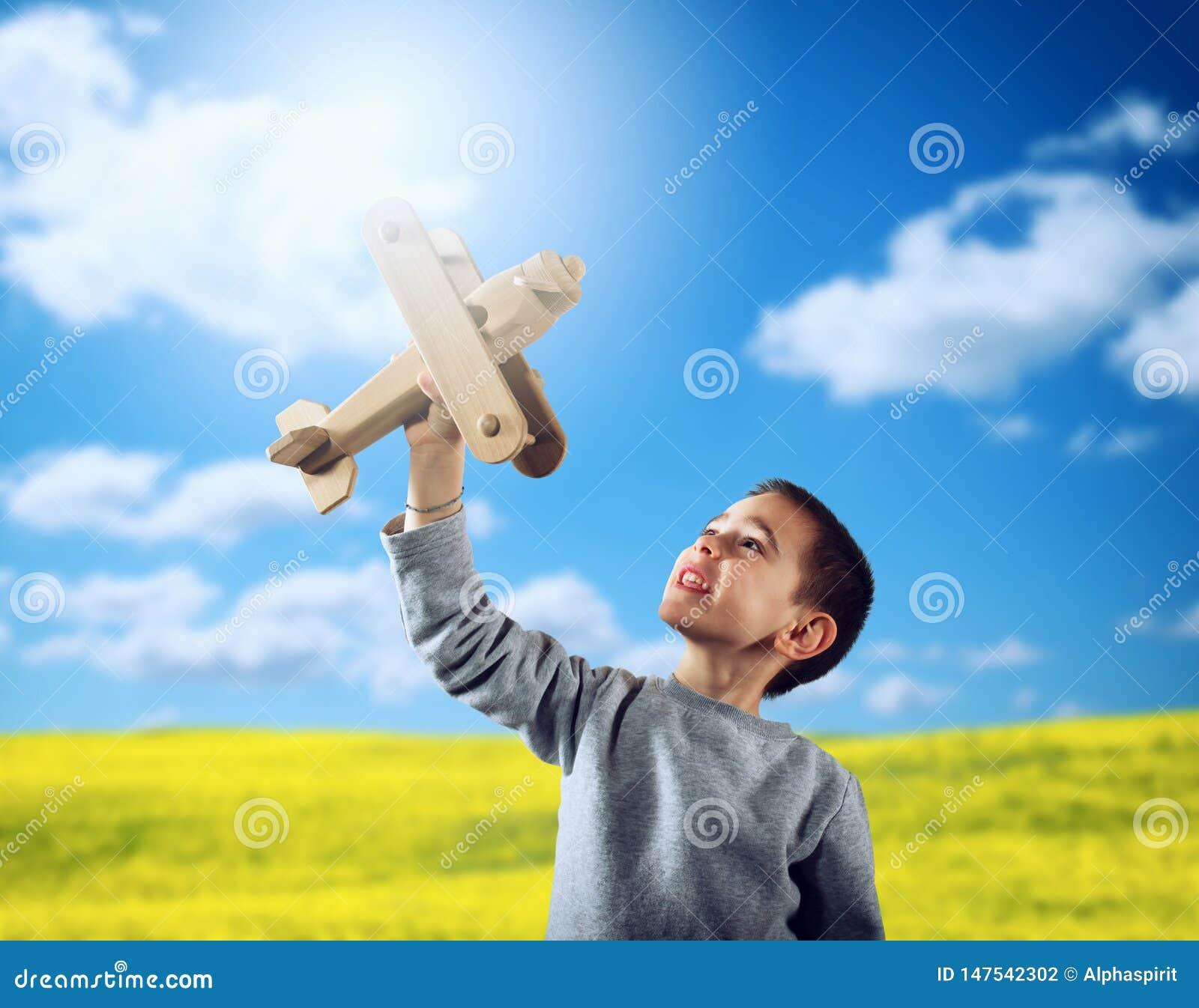Jong geitjespelen met een houten stuk speelgoed vliegtuig