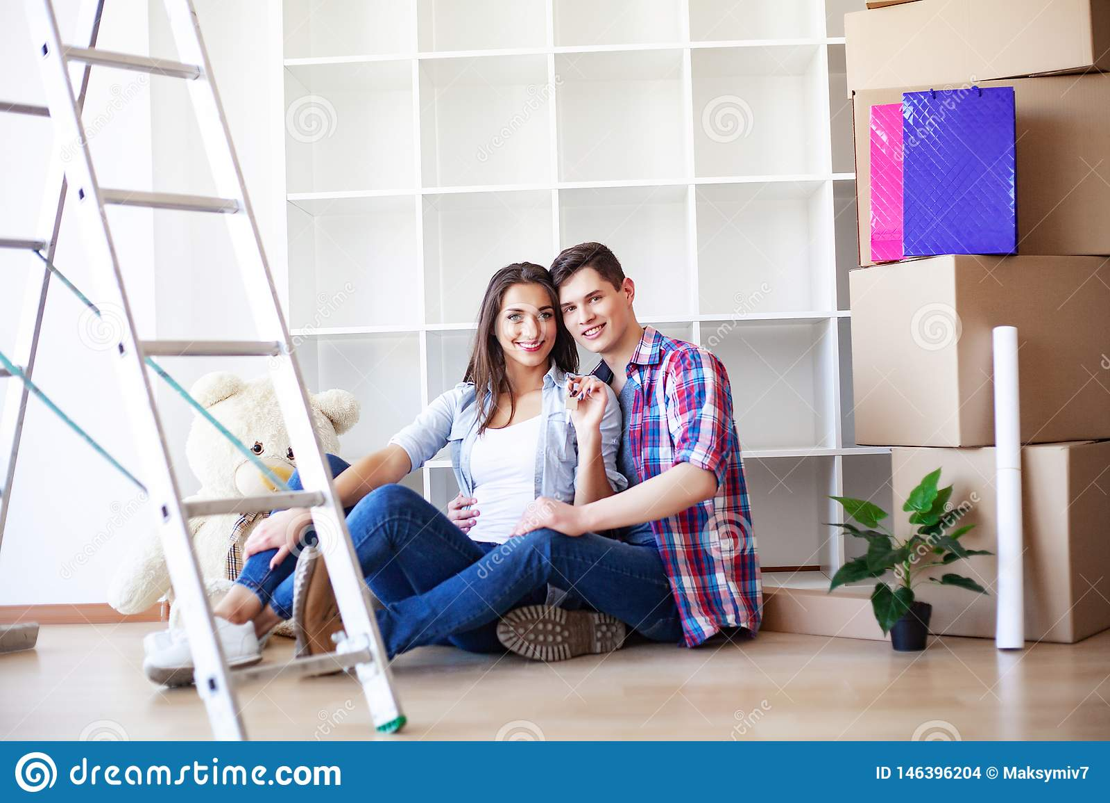 Jong gelukkig paar dat zich in hun nieuw huis beweegt Zij die en nieuw huis uitpakken schoonmaken