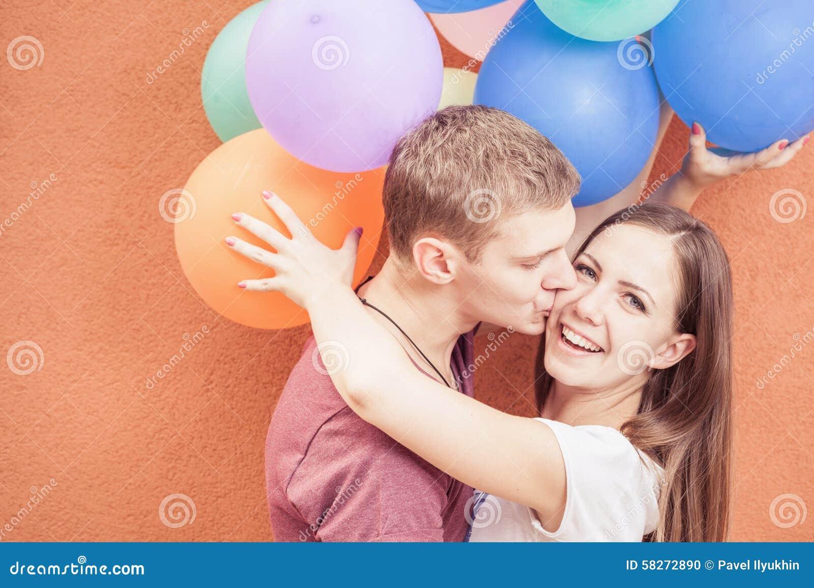 Jong gelukkig paar dichtbij de oranje muurtribune met ballons