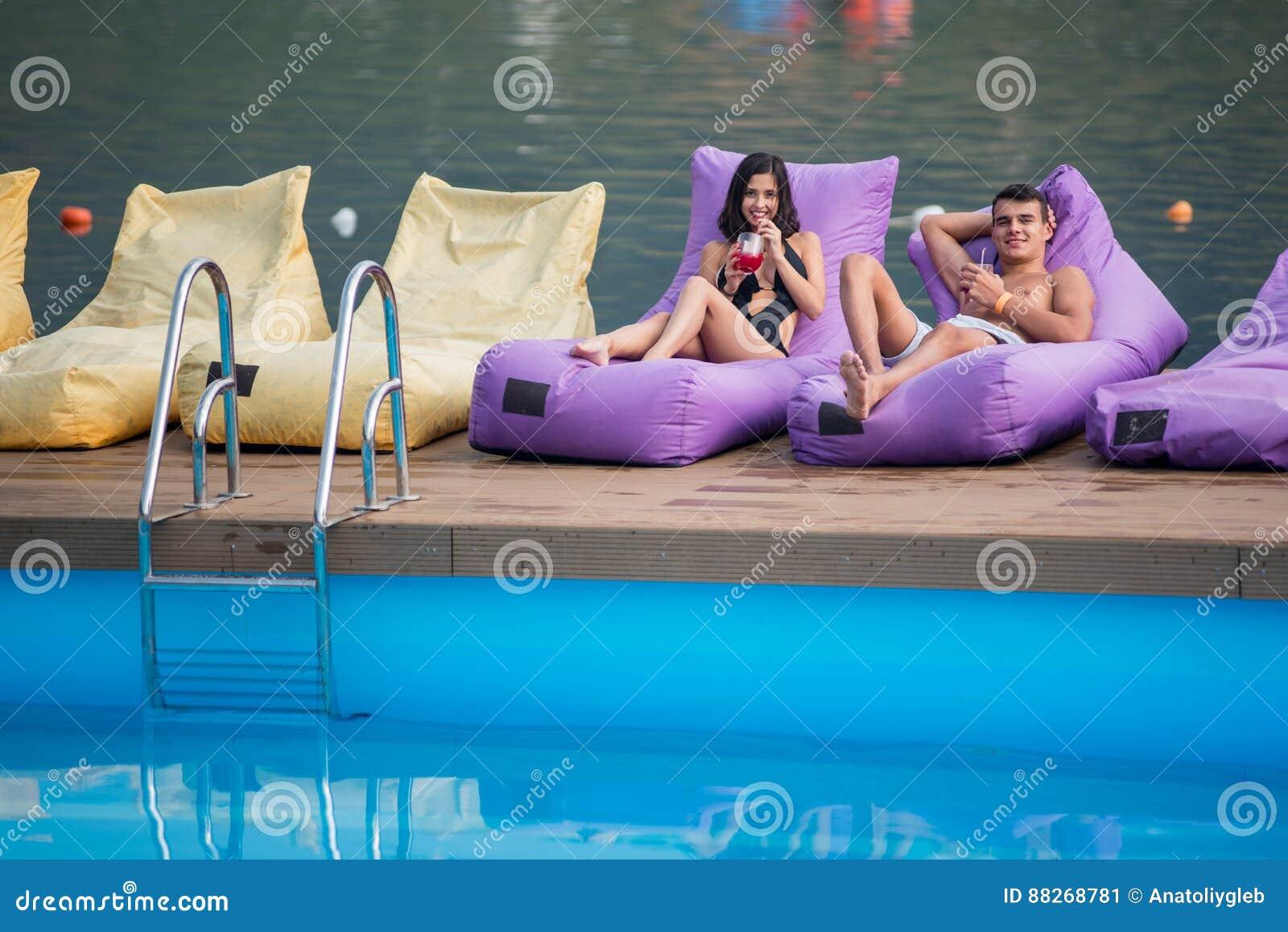 Jong gelukkig paar die met dranken op beschermde lanterfanters door zwembad op de achtergrond van rivier genieten van