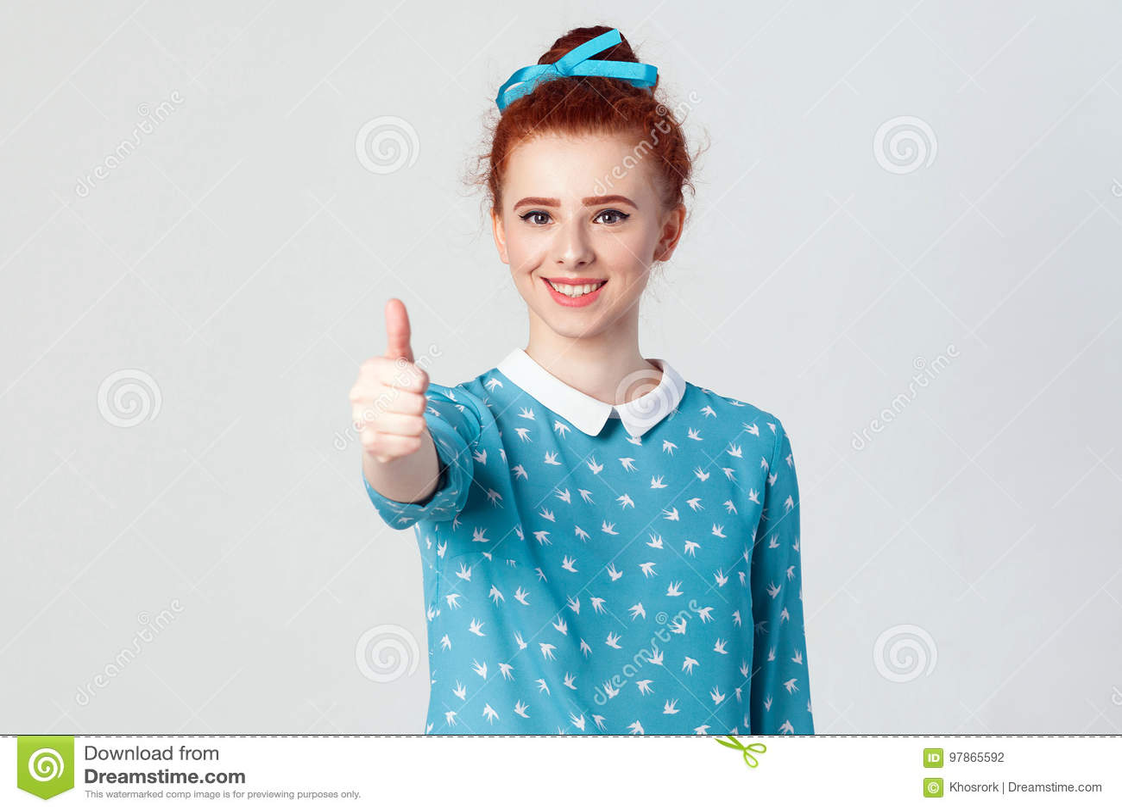 Jong gelukkig vrolijk roodharigemeisje die duim en toothy glimlach tonen Studio die op grijze achtergrond is ontsproten