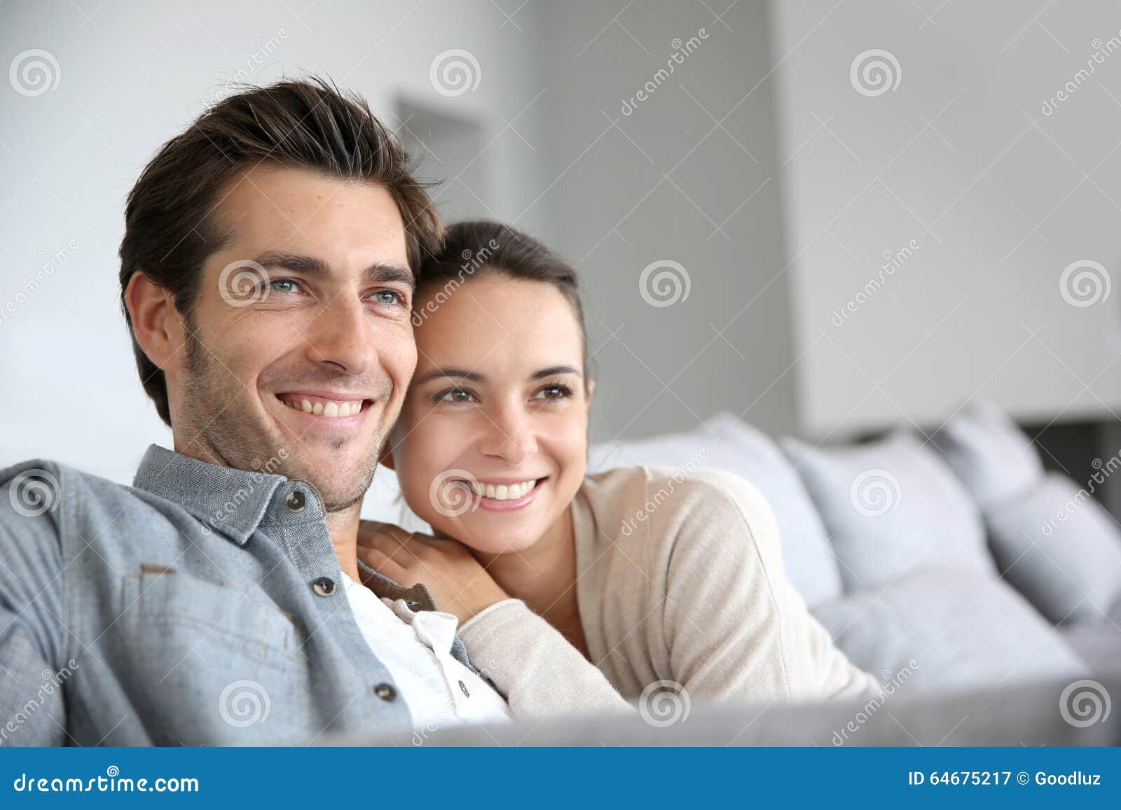 Jong glimlachend paar die naar toekomst kijken