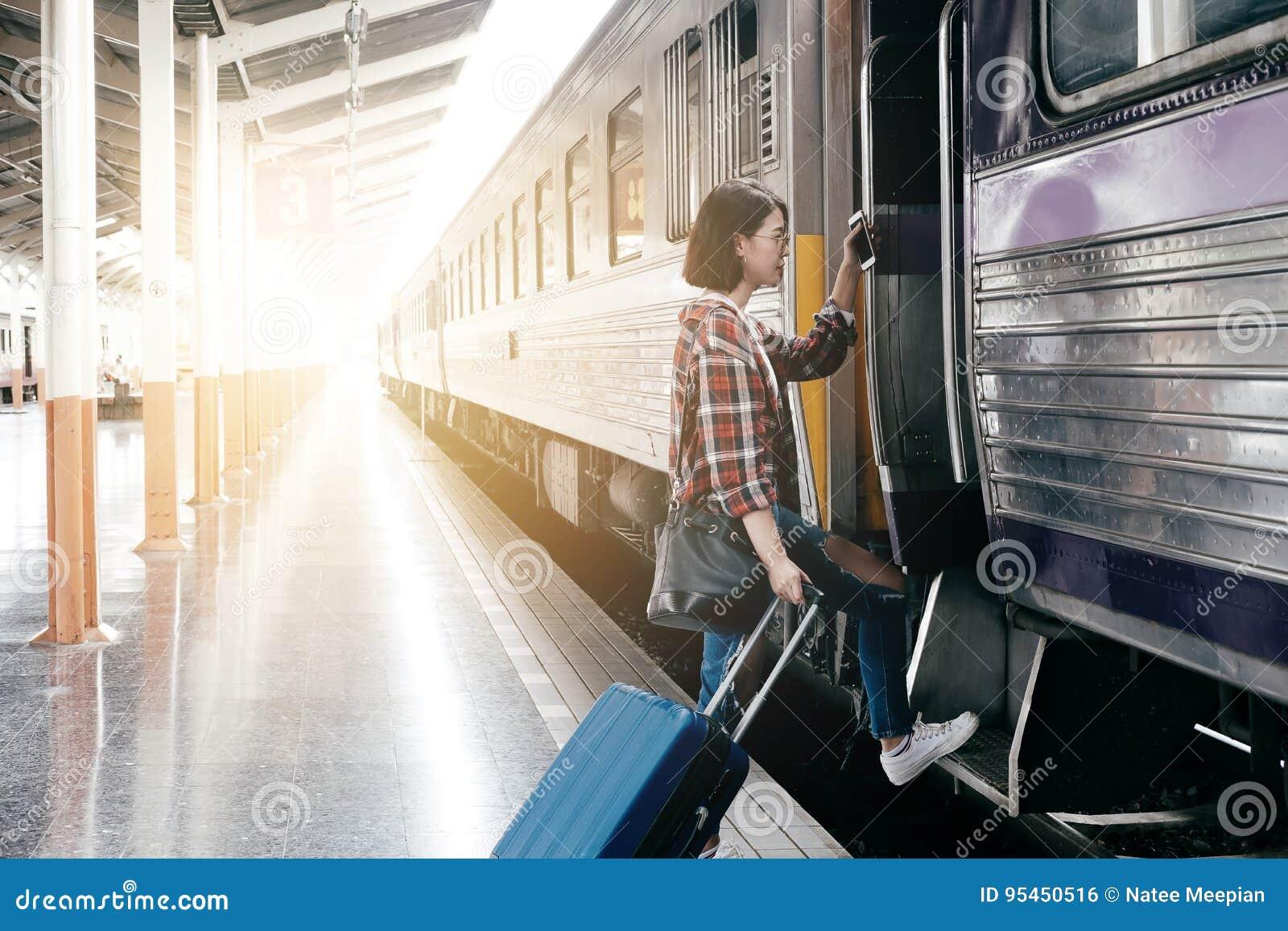 Jong Kaukasisch meisje met bagage bij post die door trein reizen