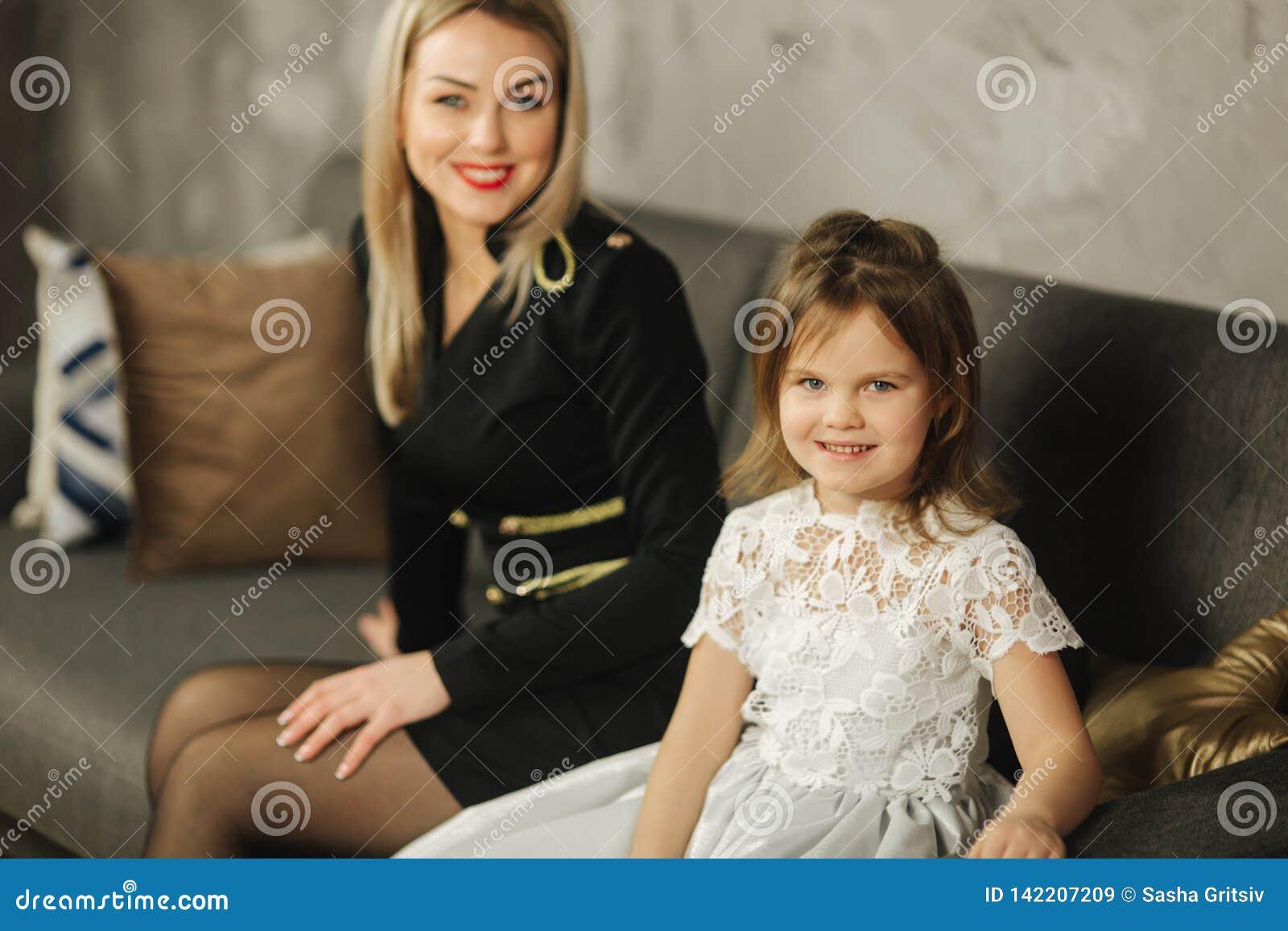 Jong mamma en weinig dochter die thuis op bank zitten Aantrekkelijke moeder in zwarte kleding Gelukkige Familie