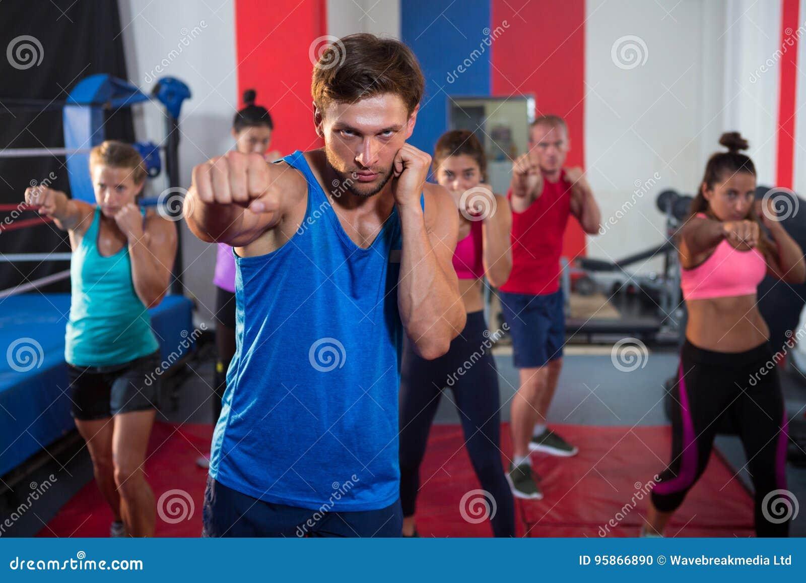 Jong mannelijk en vrouwelijk atletenponsen door boksring