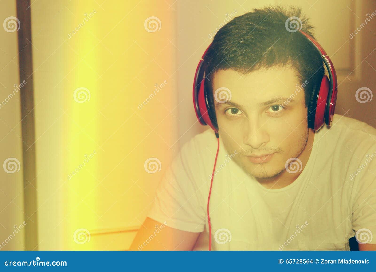 Jong mannelijk model die aan muziek bij camera thuis luisteren