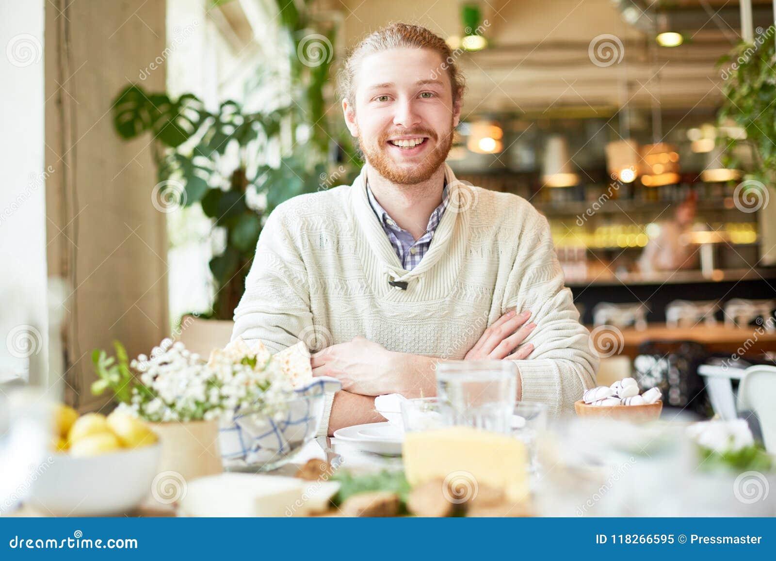 Jong mannetje die en camera in koffie glimlachen bekijken