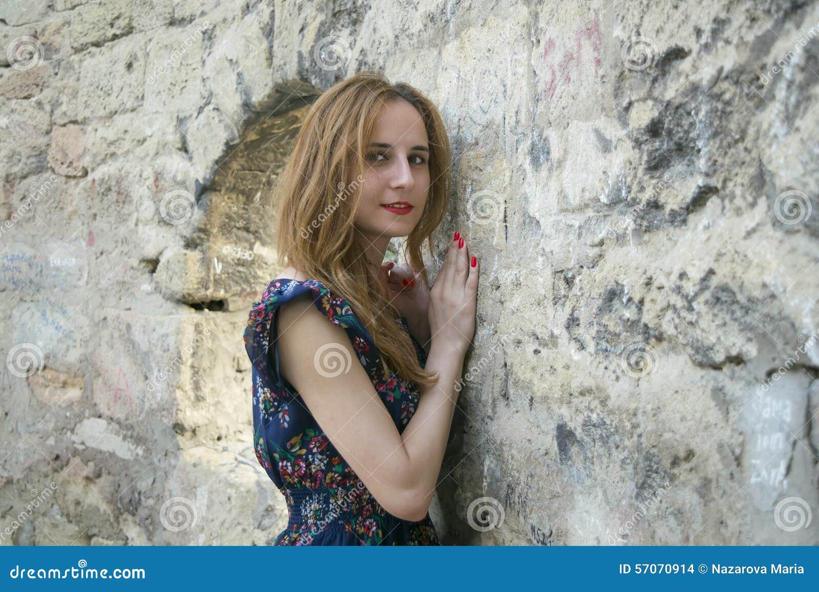 Jong meisje dichtbij een steenmuur