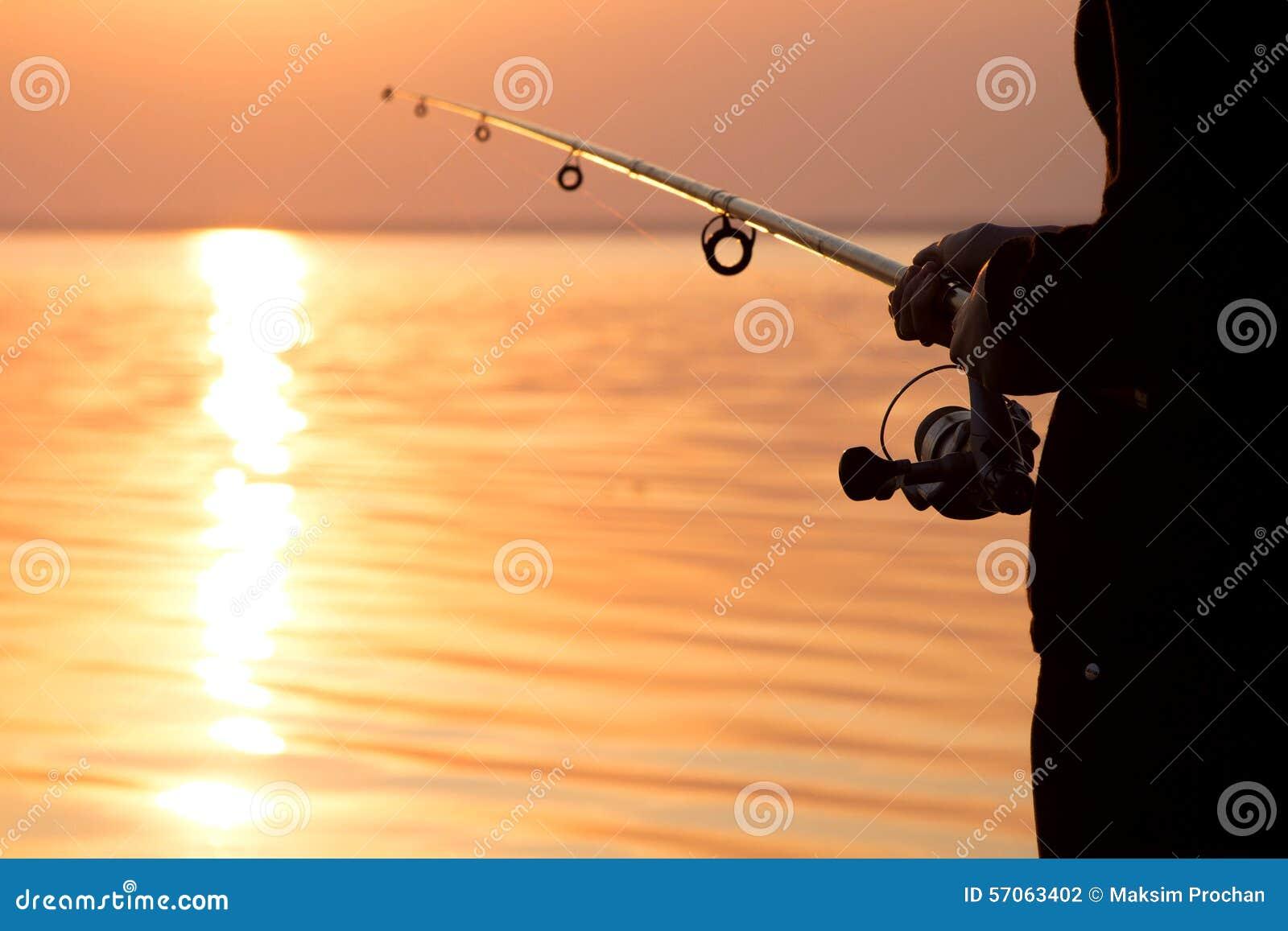 Jong meisje die bij zonsondergang dichtbij het overzees vissen