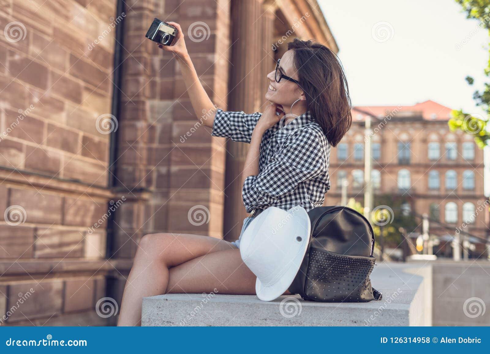 Jong meisje die een selfie met retro camera nemen