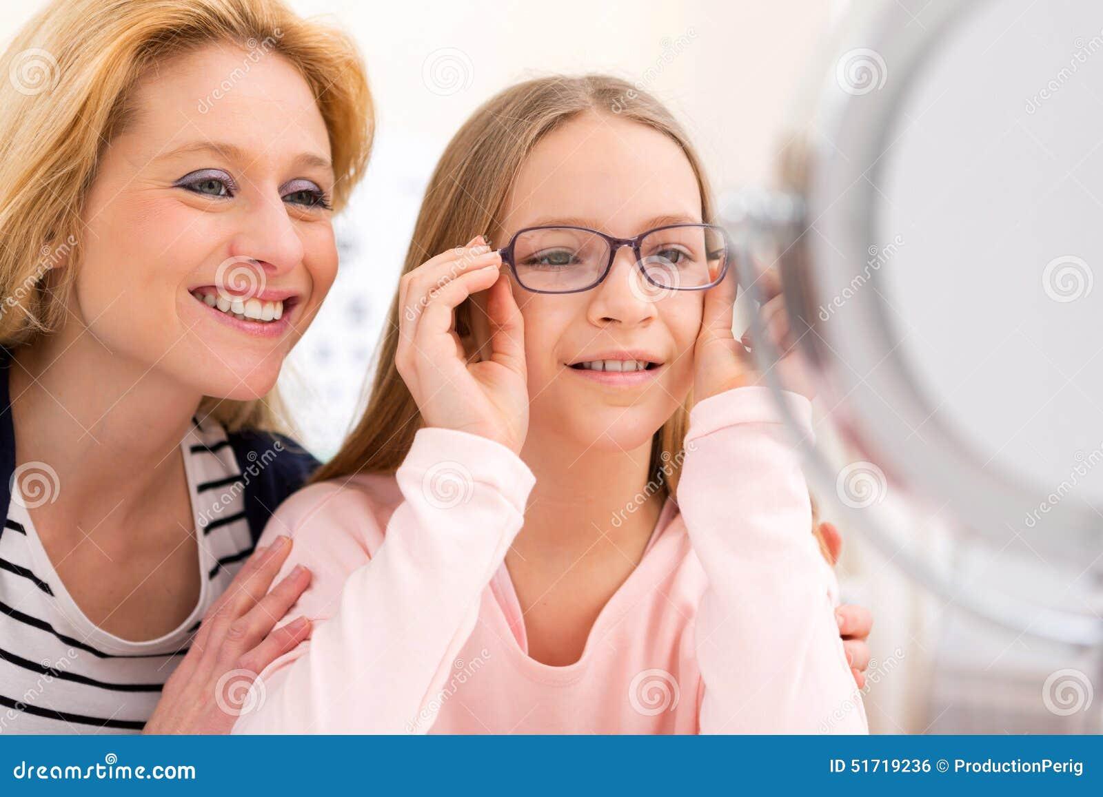 Jong meisje die glazen proberen bij de opticien w haar moeder