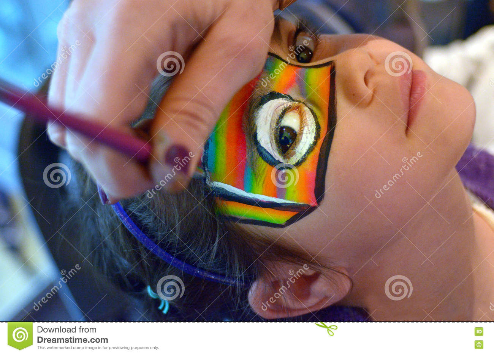 Jong meisje die haar die gezicht krijgen in regenboogkleuren wordt geschilderd