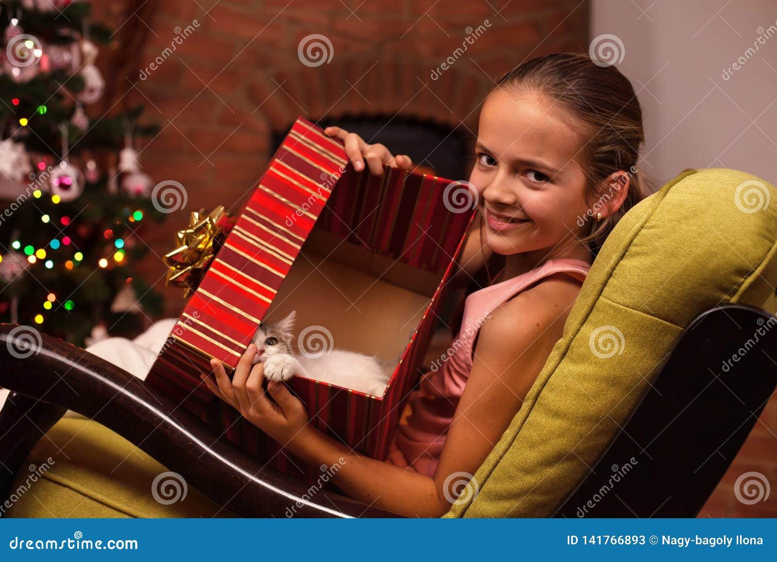 Jong meisje die haar Kerstmis huidig in een grote doos tonen - een leuk katje