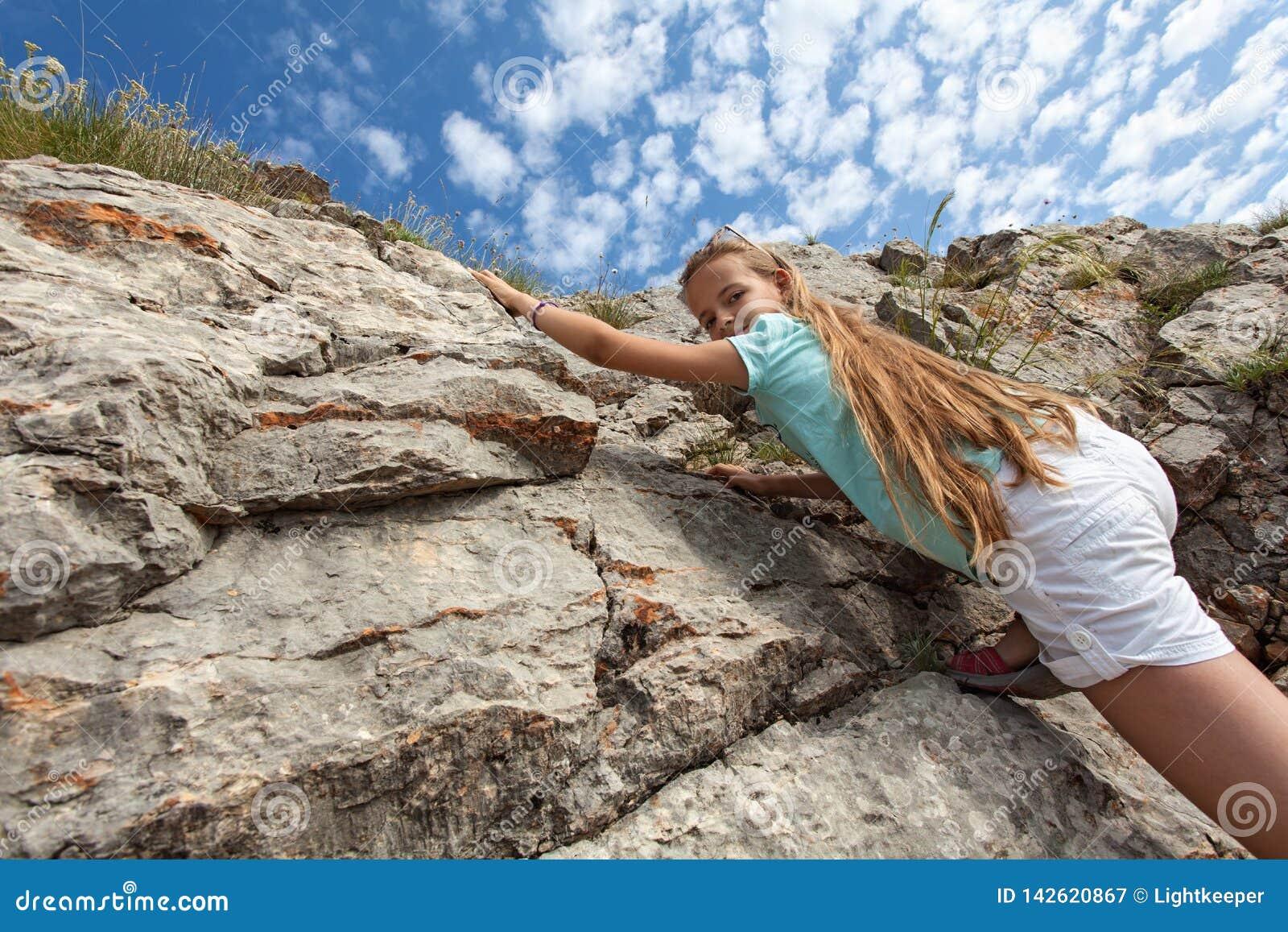 Jong meisje die - op een rotsachtige helling beklimmen wandelen die