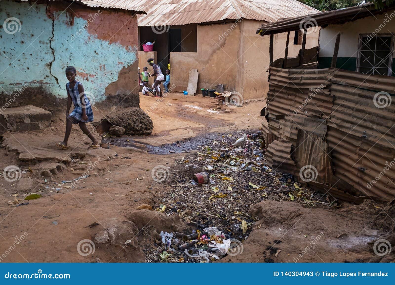 Jong meisje die op een vuilstraat in een krottenwijk met een openluchtriool, bij de stad van Bissau lopen