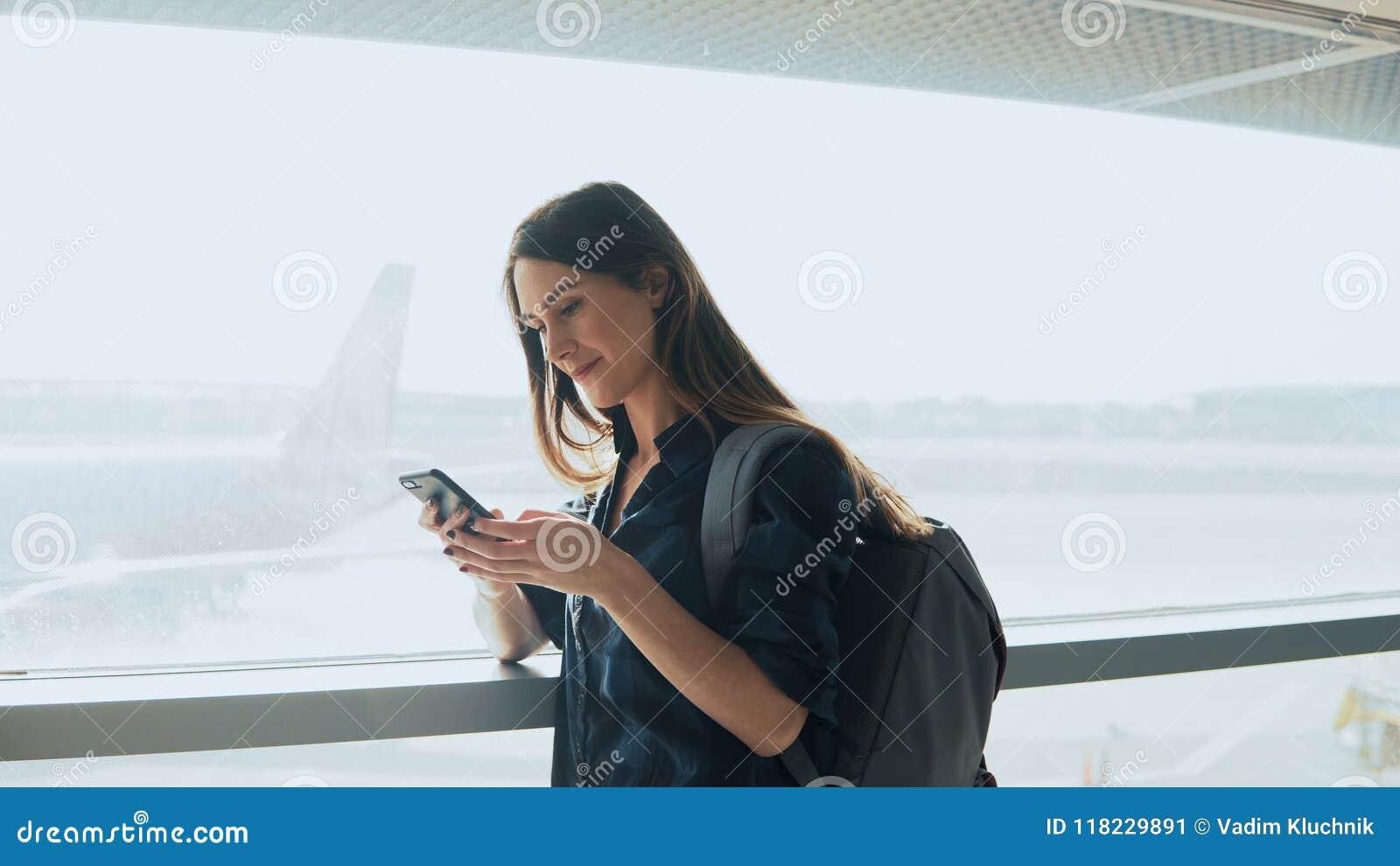 Jong meisje die smartphone gebruiken dichtbij luchthavenvenster De gelukkige Europese vrouw met rugzak gebruikt mobiele app in te