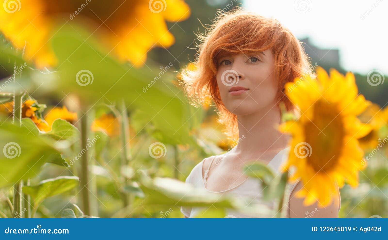 Jong meisje die van aard op het gebied van zonnebloemen genieten bij zonsondergang,