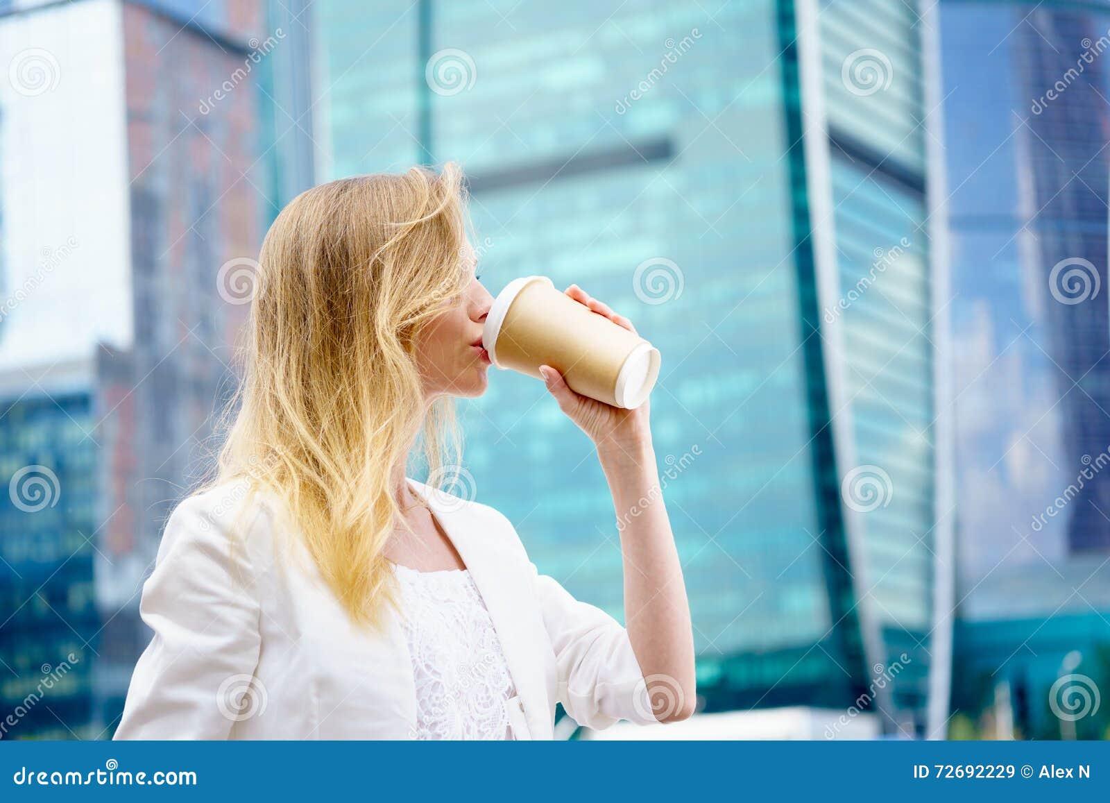 Jong meisje in het drinken van koffie in de straat