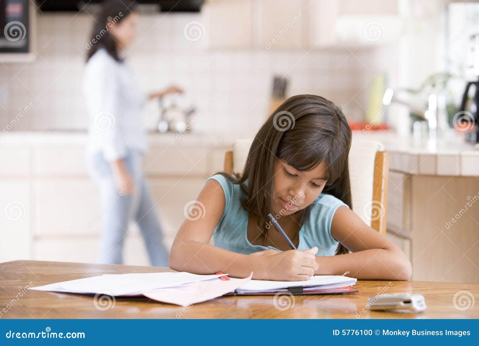 Jong meisje in keuken die thuiswerk met binnen vrouw doet
