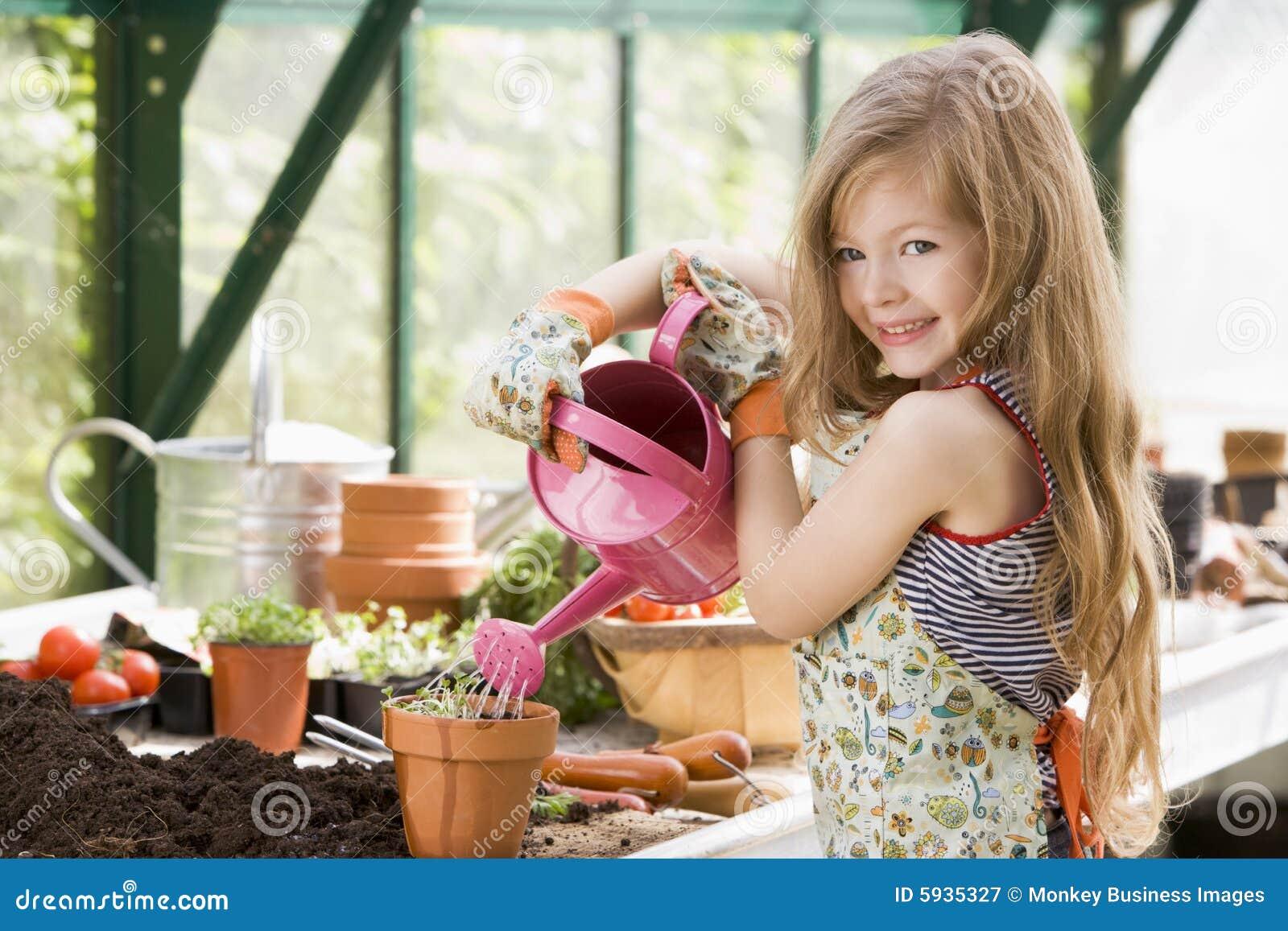 Jong meisje in serre het water geven ingemaakte installatie