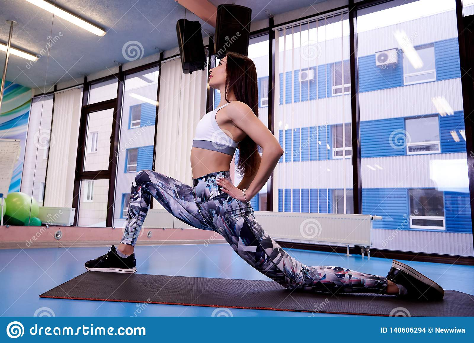 Jong mooi atletisch meisje die sport in de gymnastiek uitoefenen