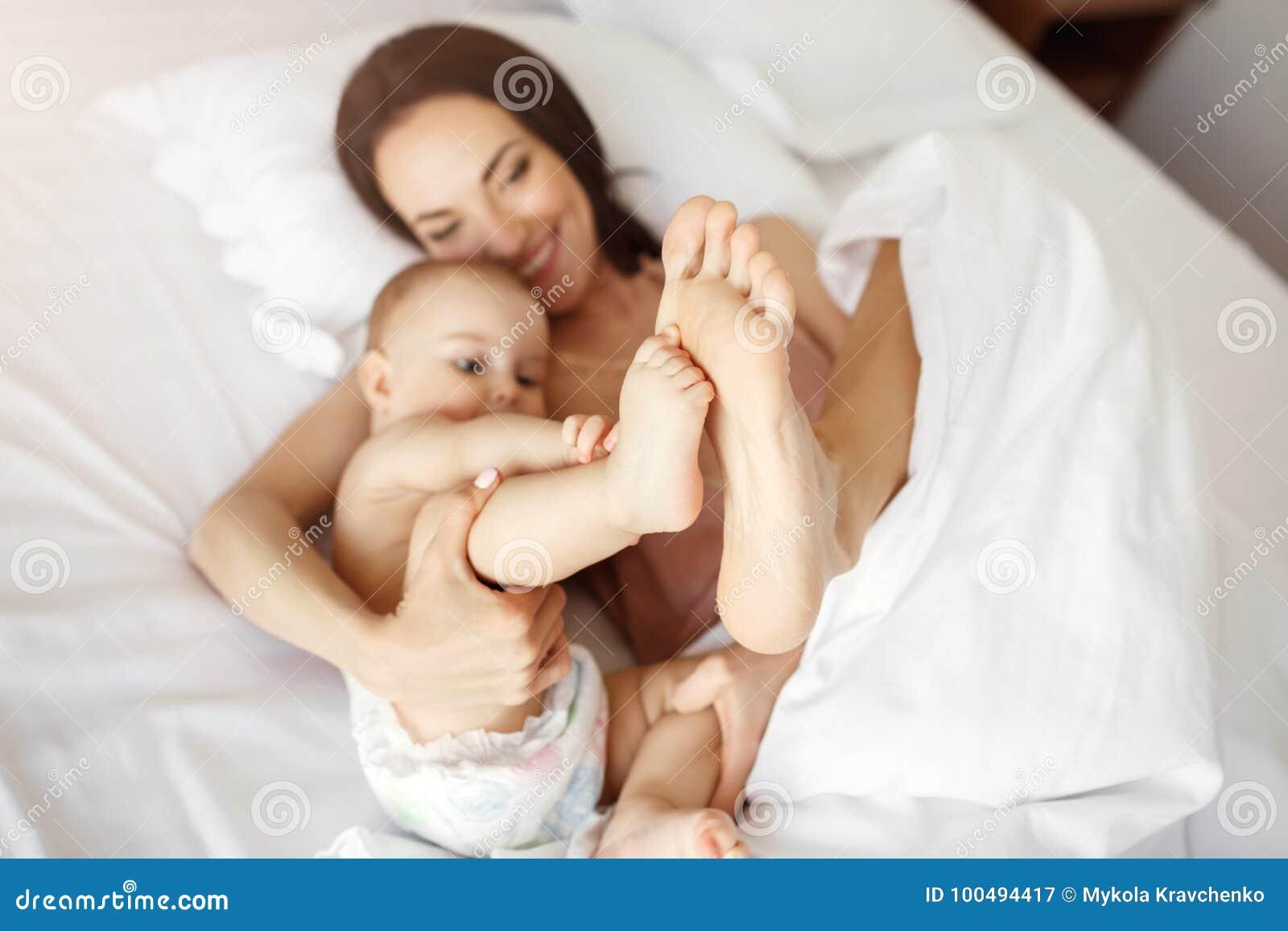Jong mooi mamma en pasgeboren baby die in bed het glimlachen thuis het voor de gek houden liggen Van hierboven