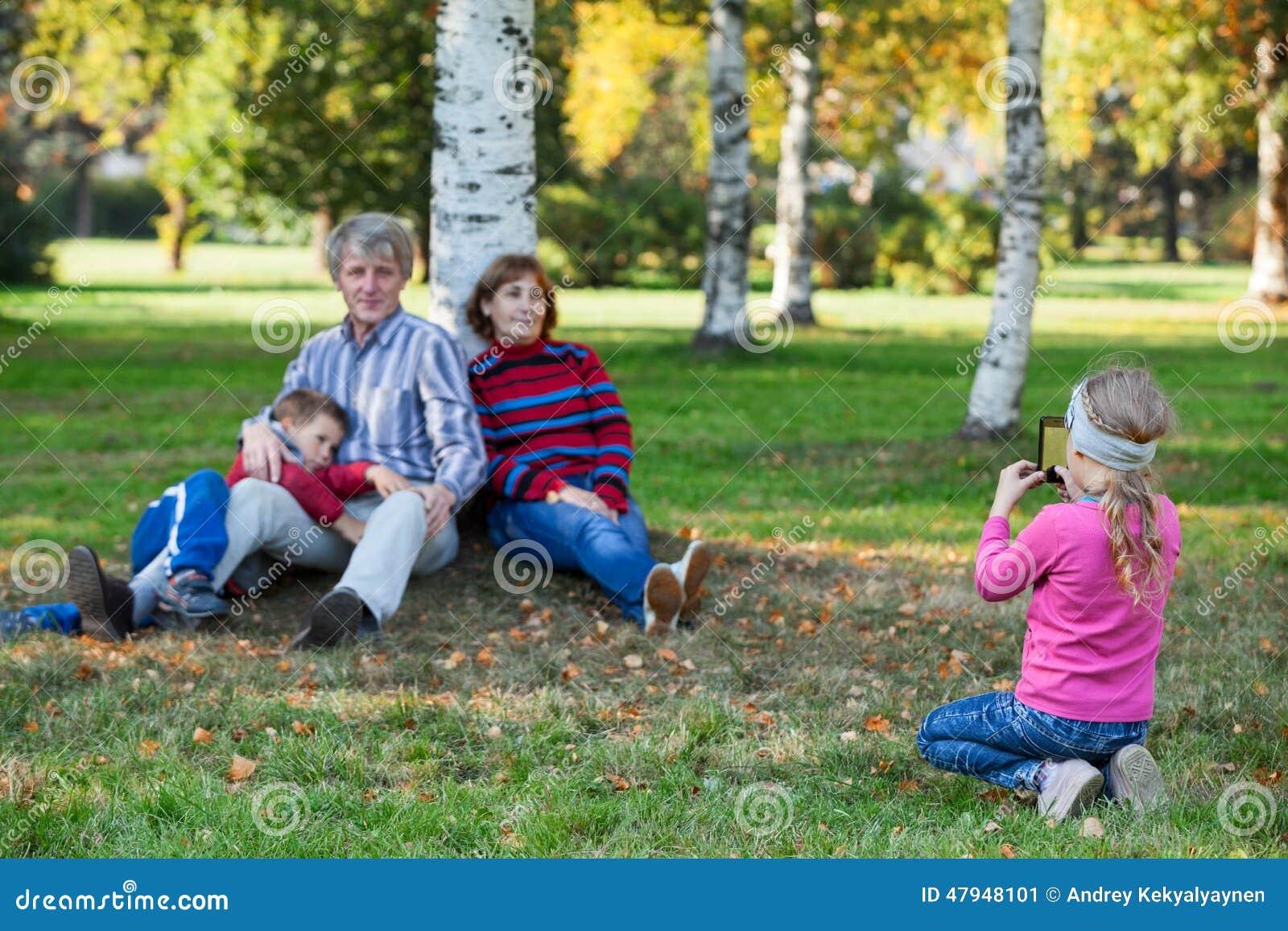Jong mooi meisje die haar familie telefonisch in de herfstpark fotograferen