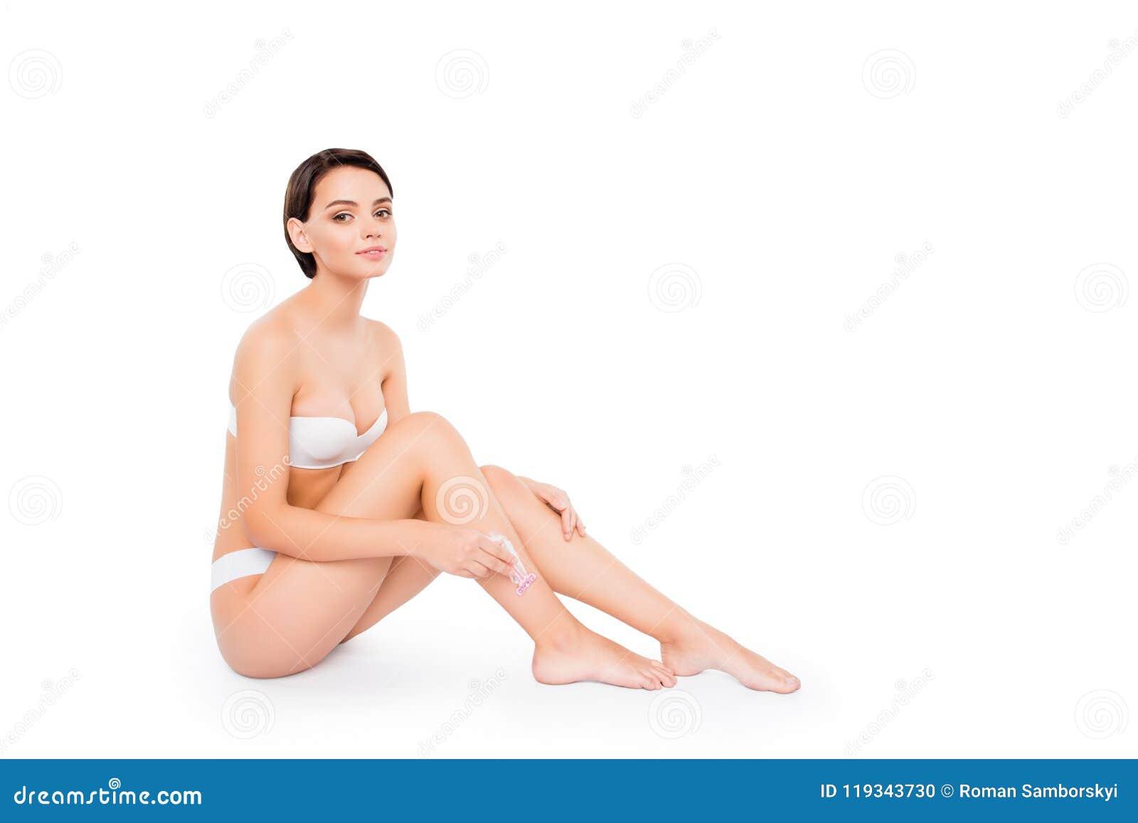 Jong mooi meisje die in lingerie haar die benen met scheermes scheren op witte schone duidelijke achtergrond wordt geïsoleerd Lic